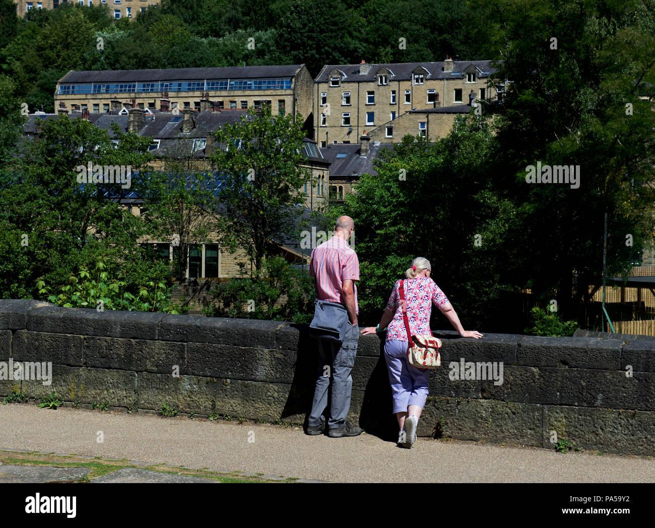 Couple on canal towpath, looking over bridge, Hebden Bridge, Calderdale, West Yorkshire, England UK - Stock Image
