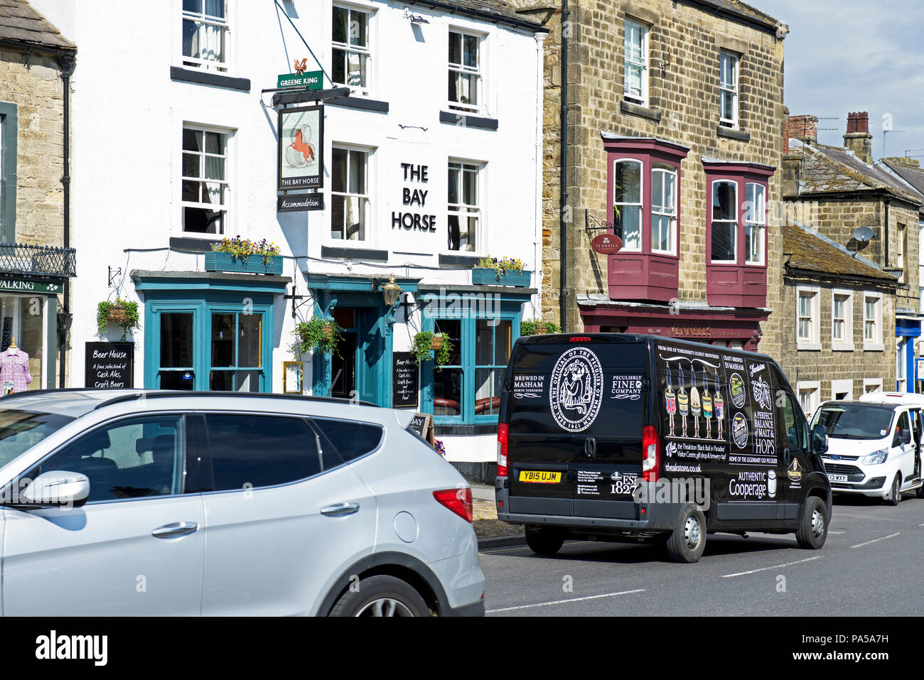 Theakston Brewery delivery van, passing the Bay Horse pub, Masham, North Yorkshire, England UK - Stock Image