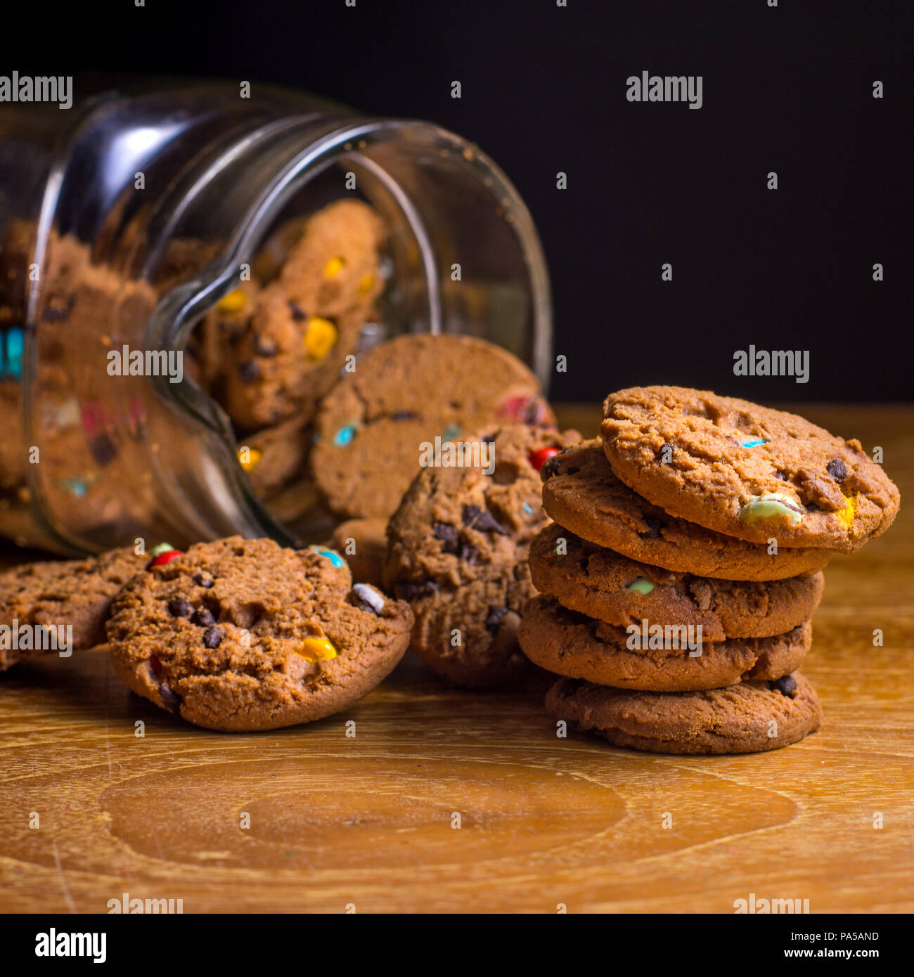 Choc chip smartie cookies falling out of jar on wooden table top. Stock Photo