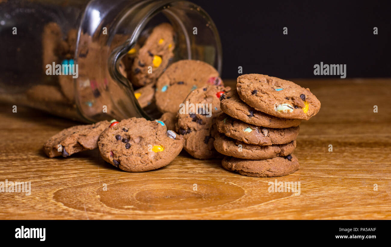 Choc chip smartie cookies falling out of jar on wooden table top. - Stock Image