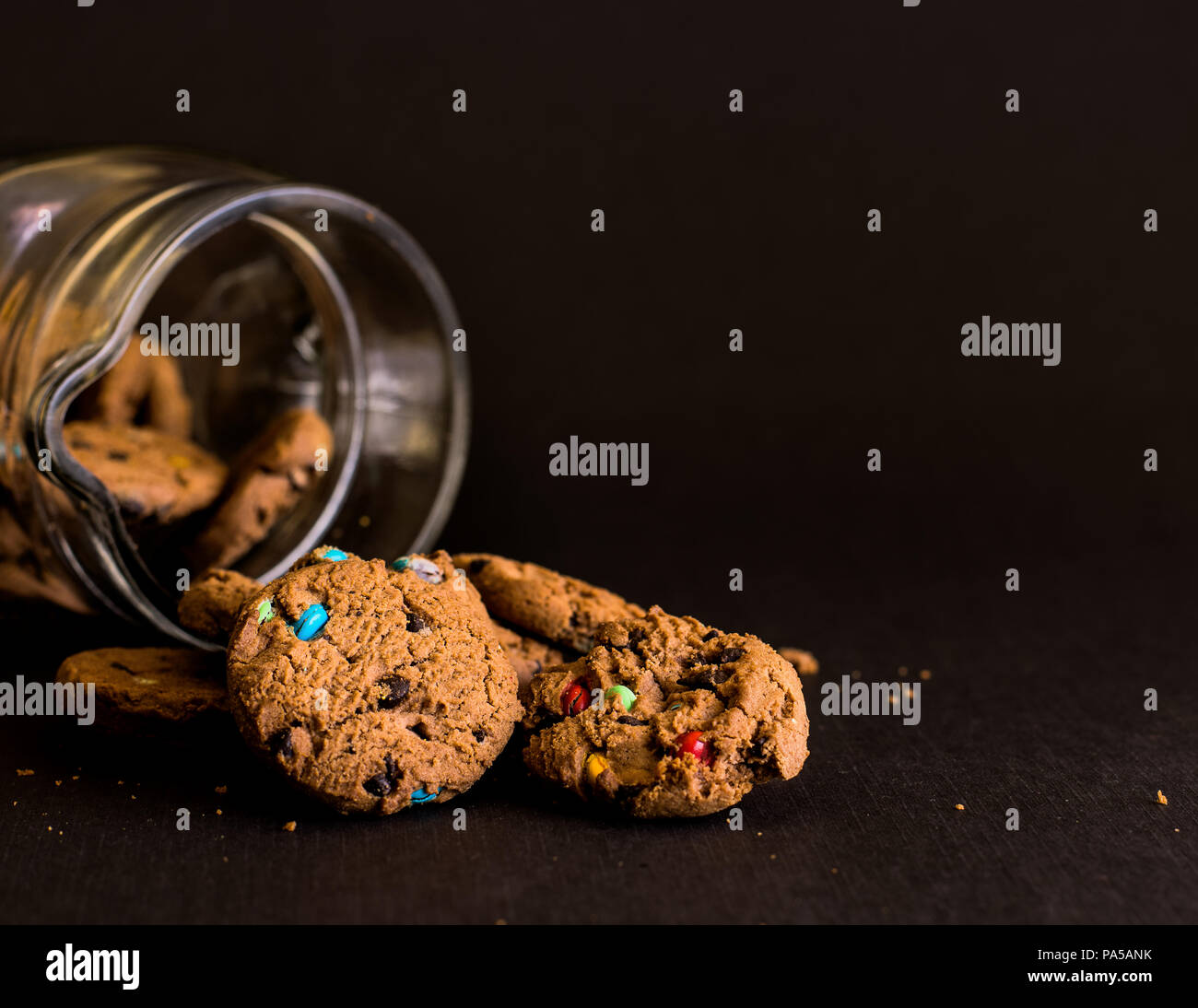 Cookie jar on black background with biscuits spilling out. - Stock Image