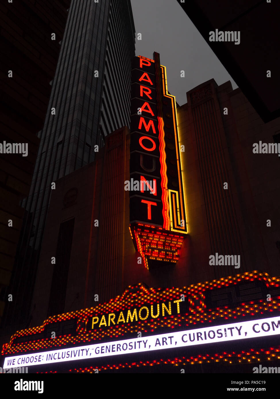 Vertical photo of Old restored Paramount theater sign lit up at night in colorful lights missing the 'U' in Paramount. - Stock Image