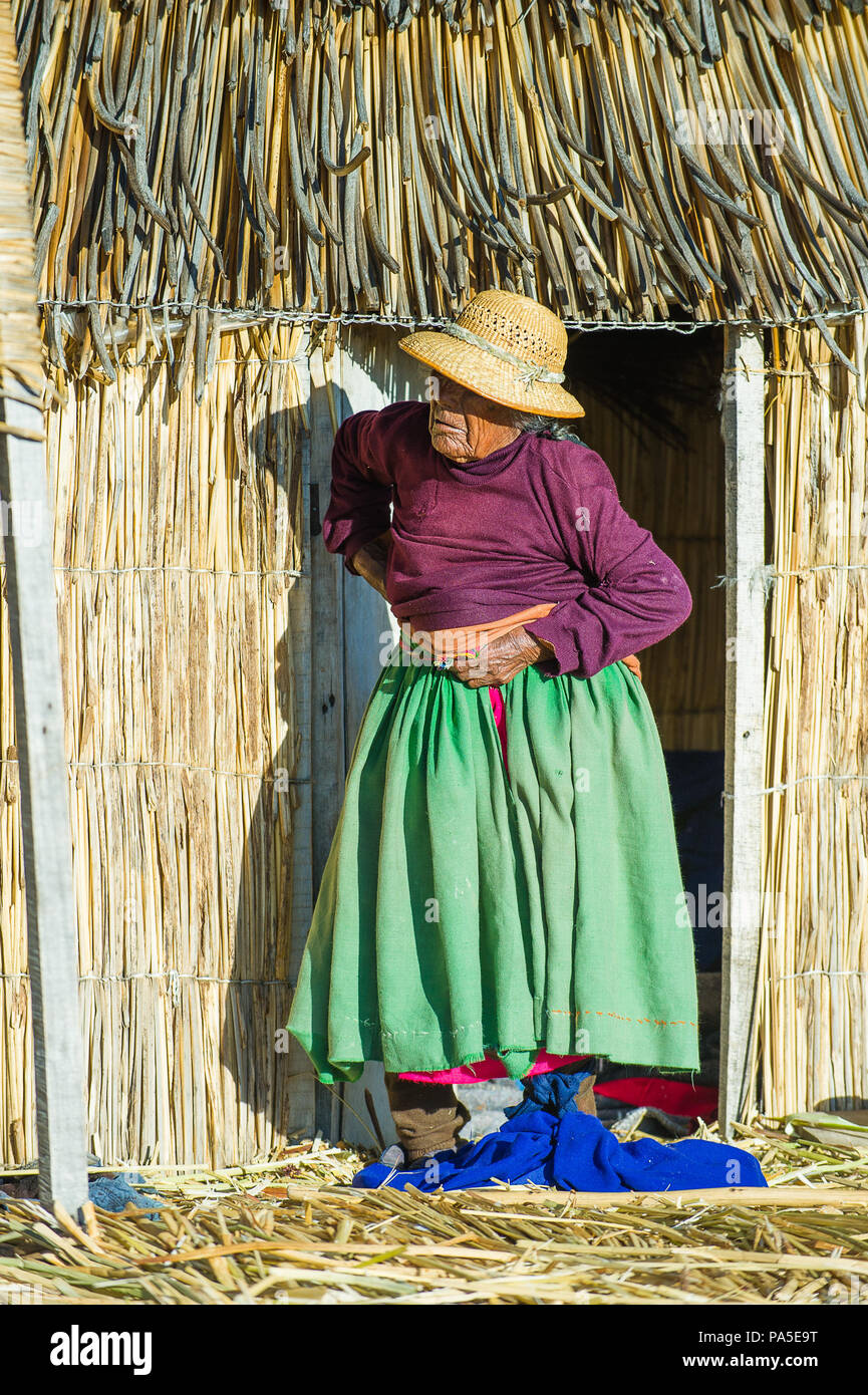 PUNO, PERU - NOVEMBER 7, 2010: Unidentified Uros woman in traditional clothes in Uros Islands, Peru, Nov 7, 2010. Uros Islands iclude 42 floating isla - Stock Image