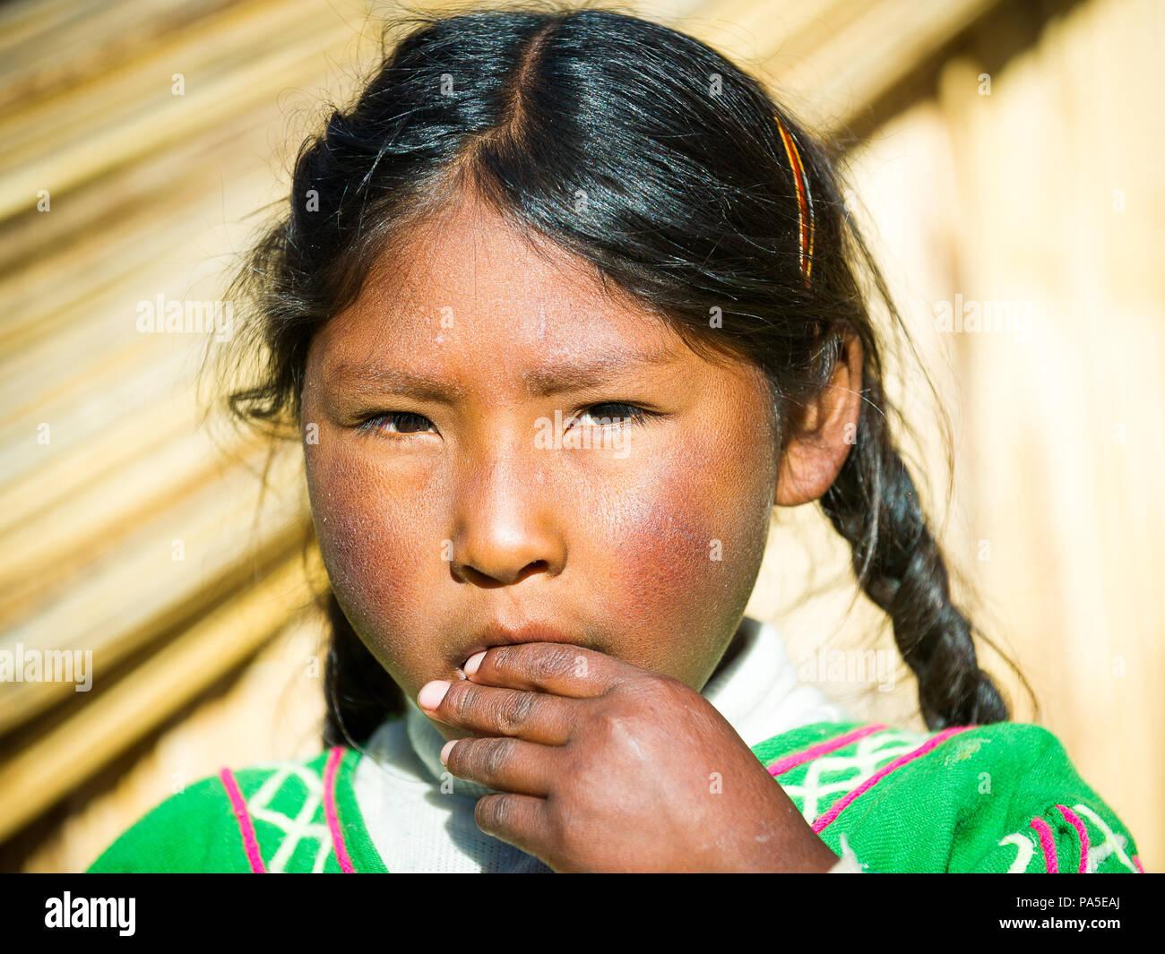 PUNO, PERU - NOVEMBER 7, 2010: Unidentified Uros girl who lives on the Uros Islands, Peru, Nov 7, 2010. Uros Islands iclude 42 floating islands. Stock Photo