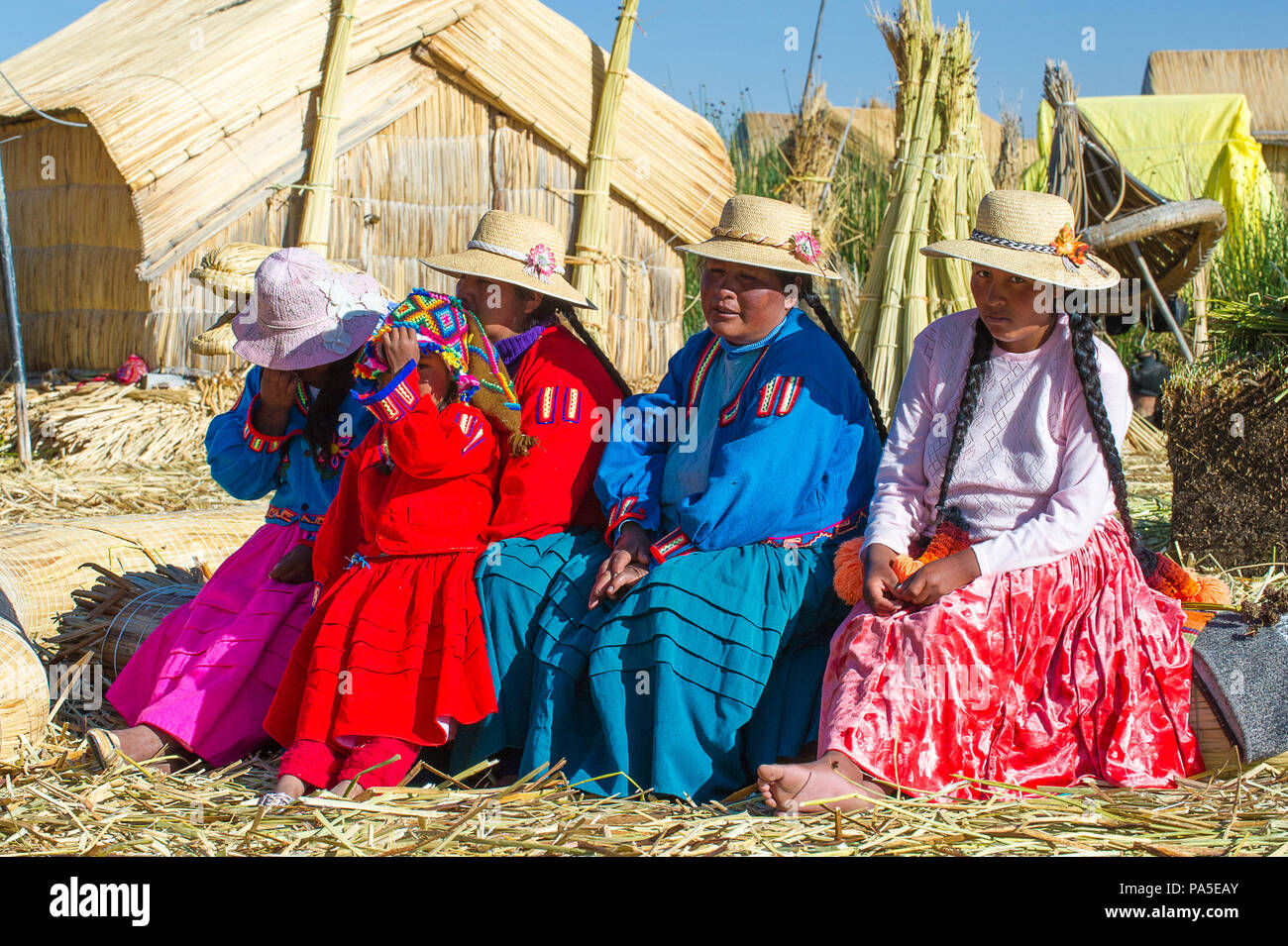 PUNO, PERU - NOVEMBER 7, 2010: Unidentified Uros people in traditional clothes on the  Uros Islands, Peru, Nov 7, 2010. Uros Islands iclude 42 floatin - Stock Image