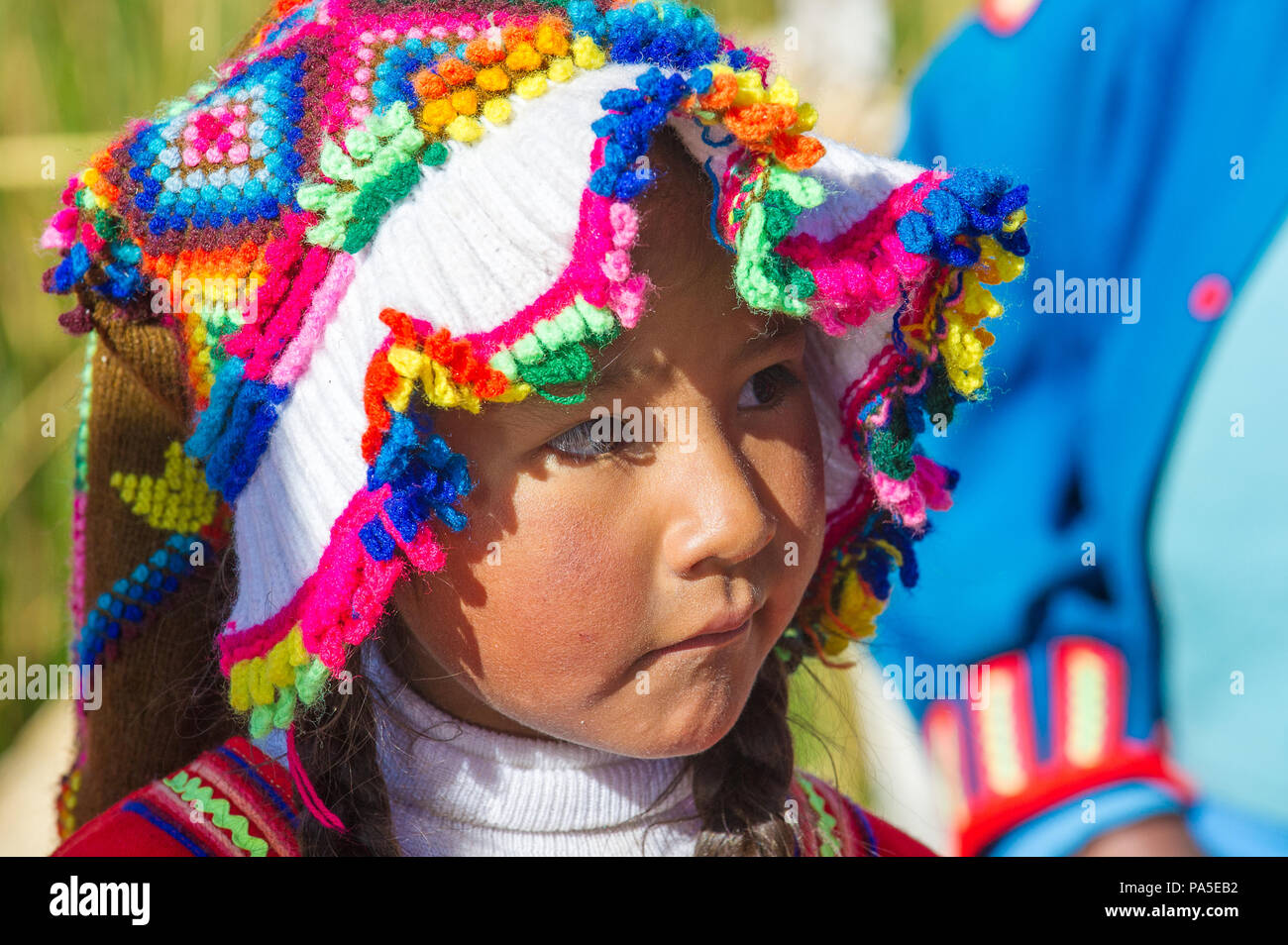 PUNO, PERU - NOVEMBER 7, 2010: Unidentified Uros girl in traditional clothes on the  Uros Islands, Peru, Nov 7, 2010. Uros Islands iclude 42 floating  - Stock Image