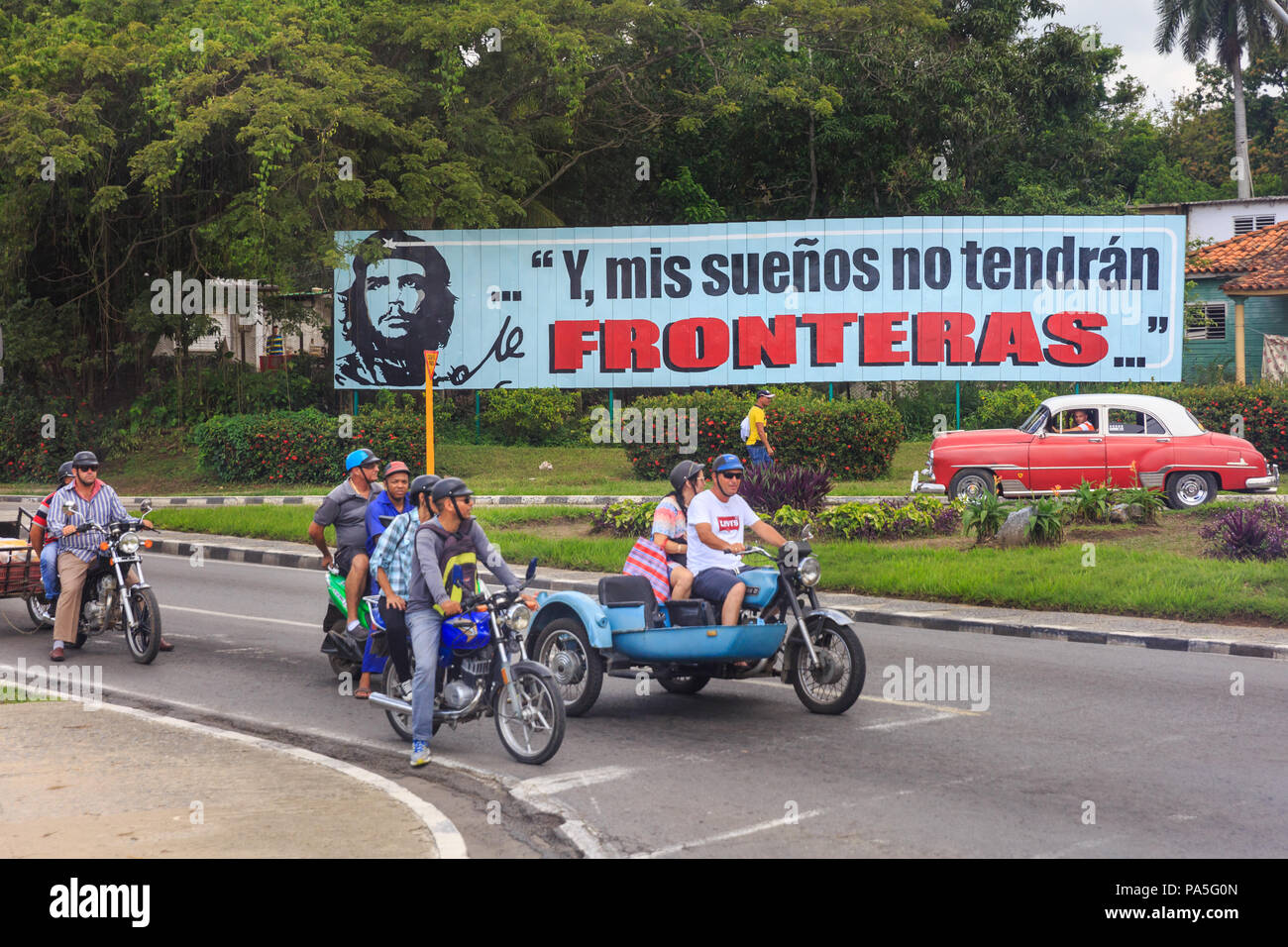 Cuban people in cars and motorcycles in front of propaganda billboard sign depicting Che Guevara, y mis suenos no tendran fronteras, Vinales, Cuba - Stock Image