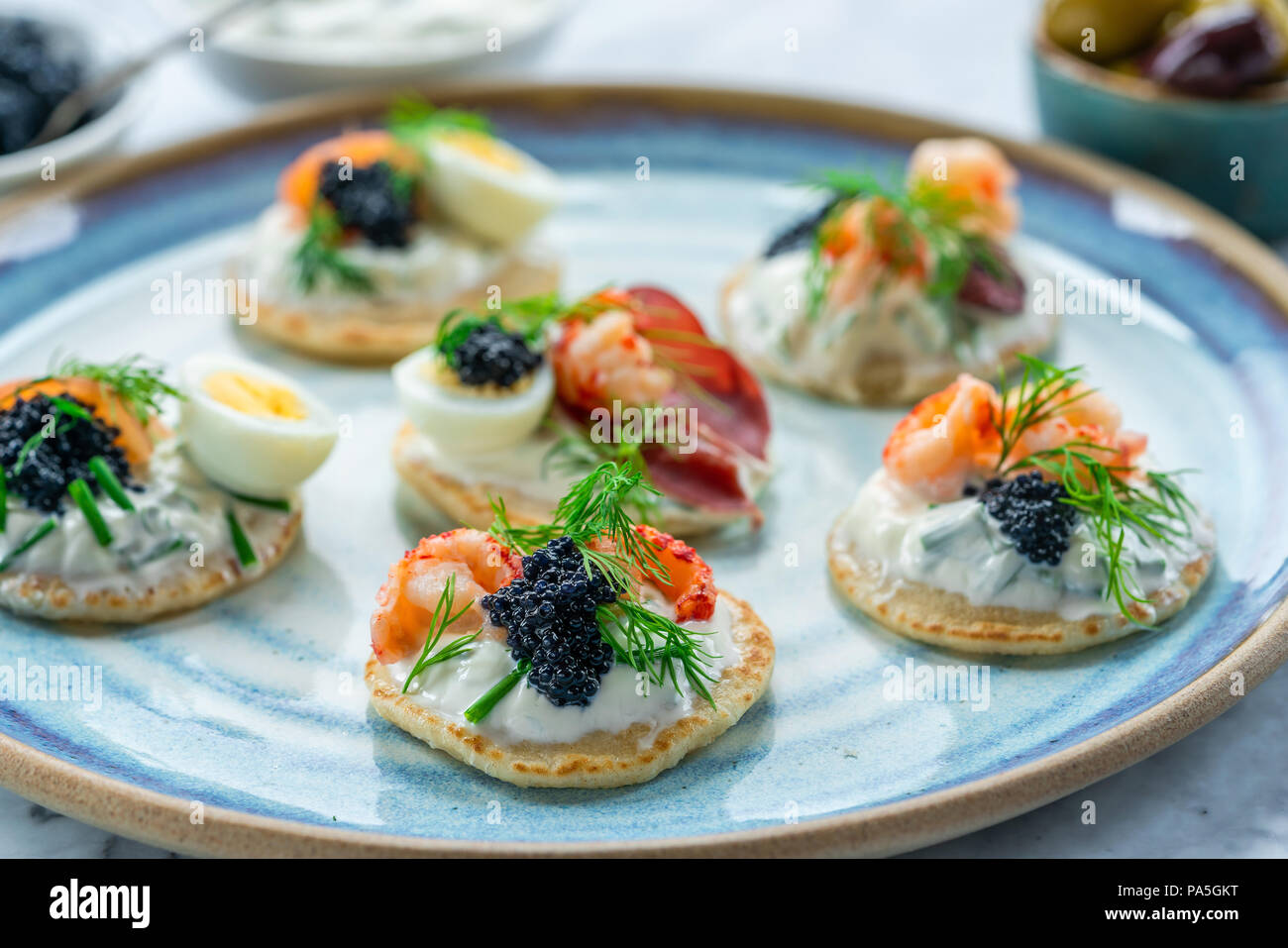 Selection of cocktail blinis with salmon, cured bresaola, crayfish, caviar, quail eggs and sour cream - gourmet party food Stock Photo