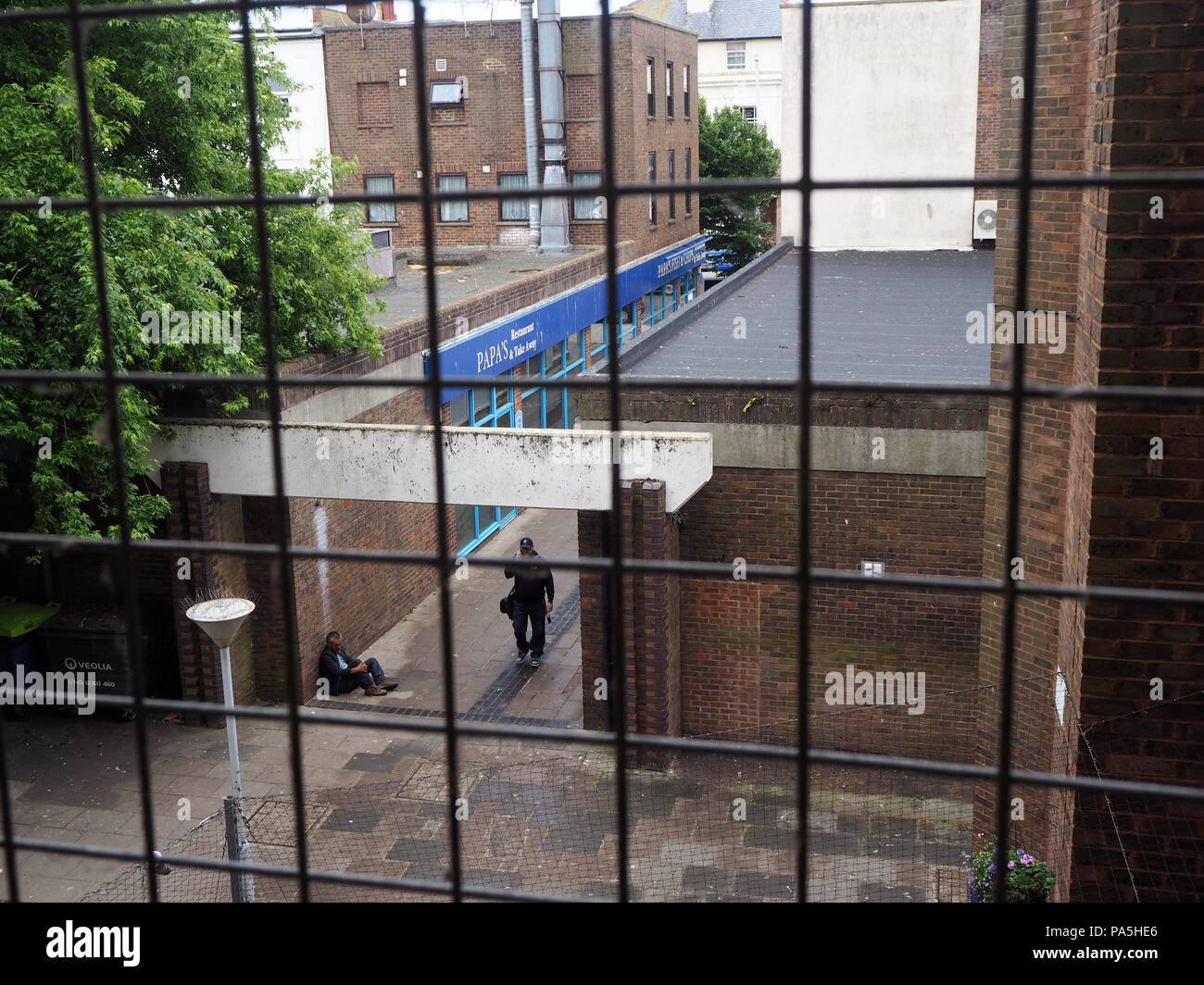 Person ignoring homeless person sitting in walkway begging - Stock Image