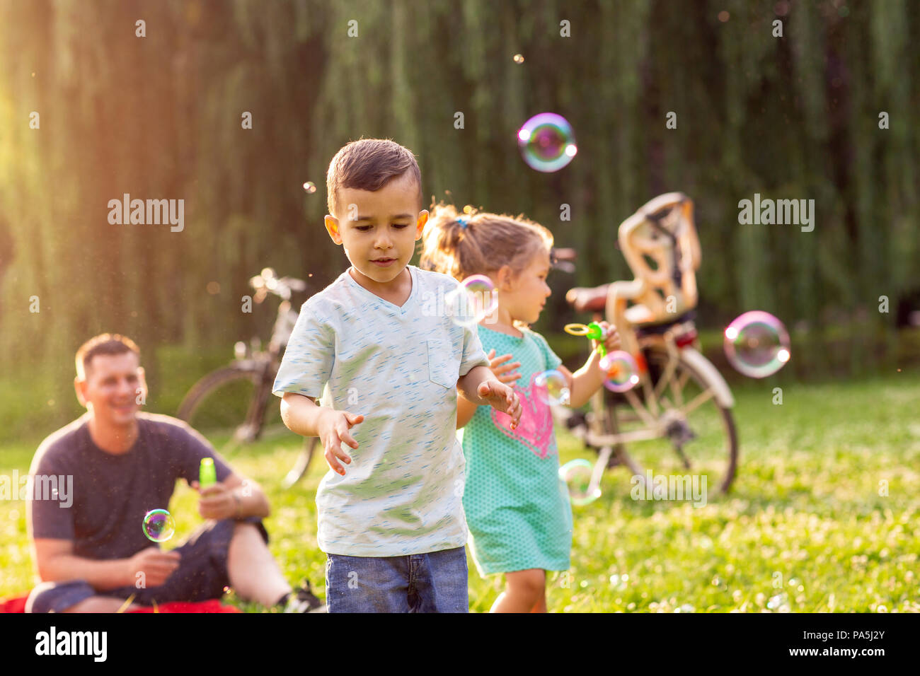 family time- Cheerful cute children chase bubbles in nature - Stock Image