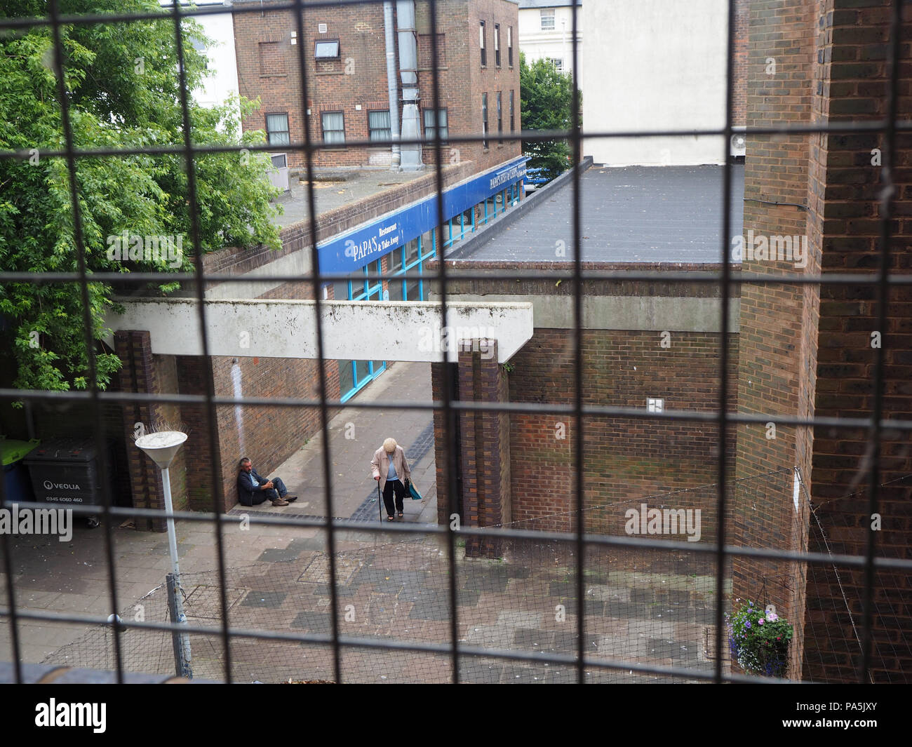 Homeless person sitting in walkway begging - Stock Image