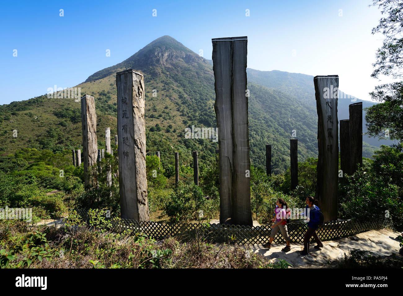 Hikers in front of wooden stelae at Wisdom Path, Lantau Peak, Lantau Island, Hong Kong, China - Stock Image