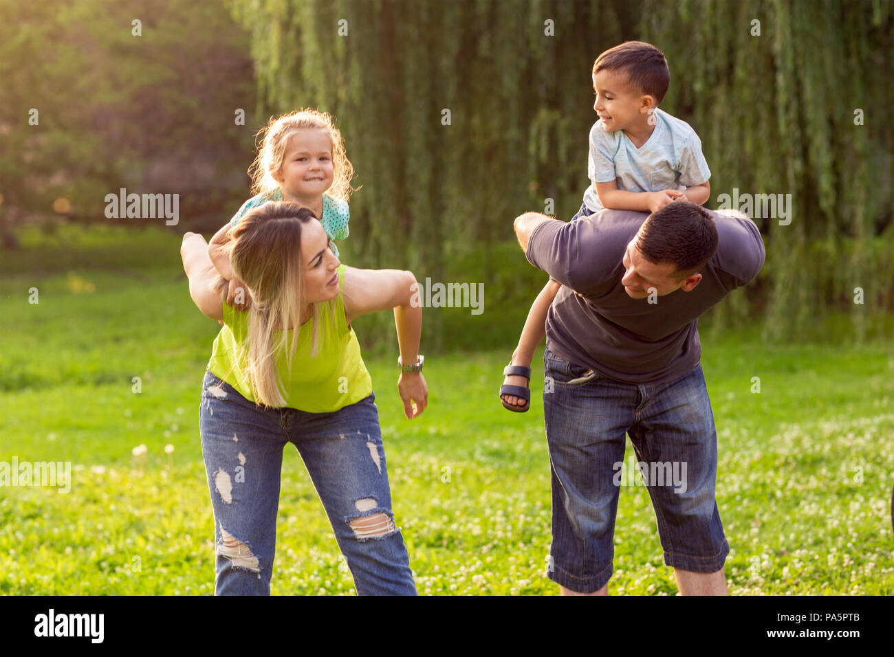 Happy parents giving piggyback ride to children - Stock Image