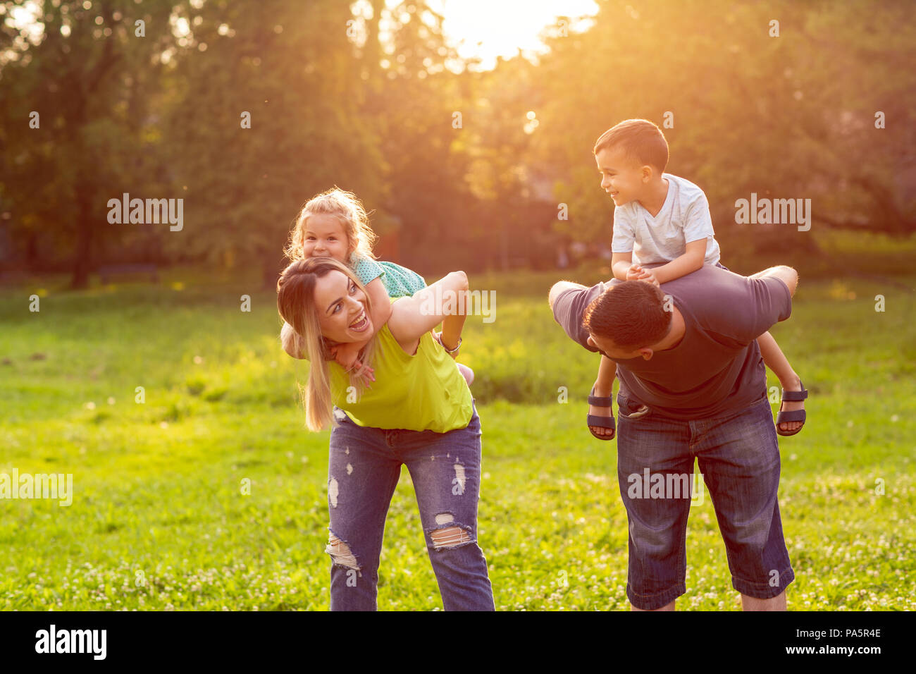 family, happiness, childhood and people concept - Happy parents giving piggyback ride to children - Stock Image