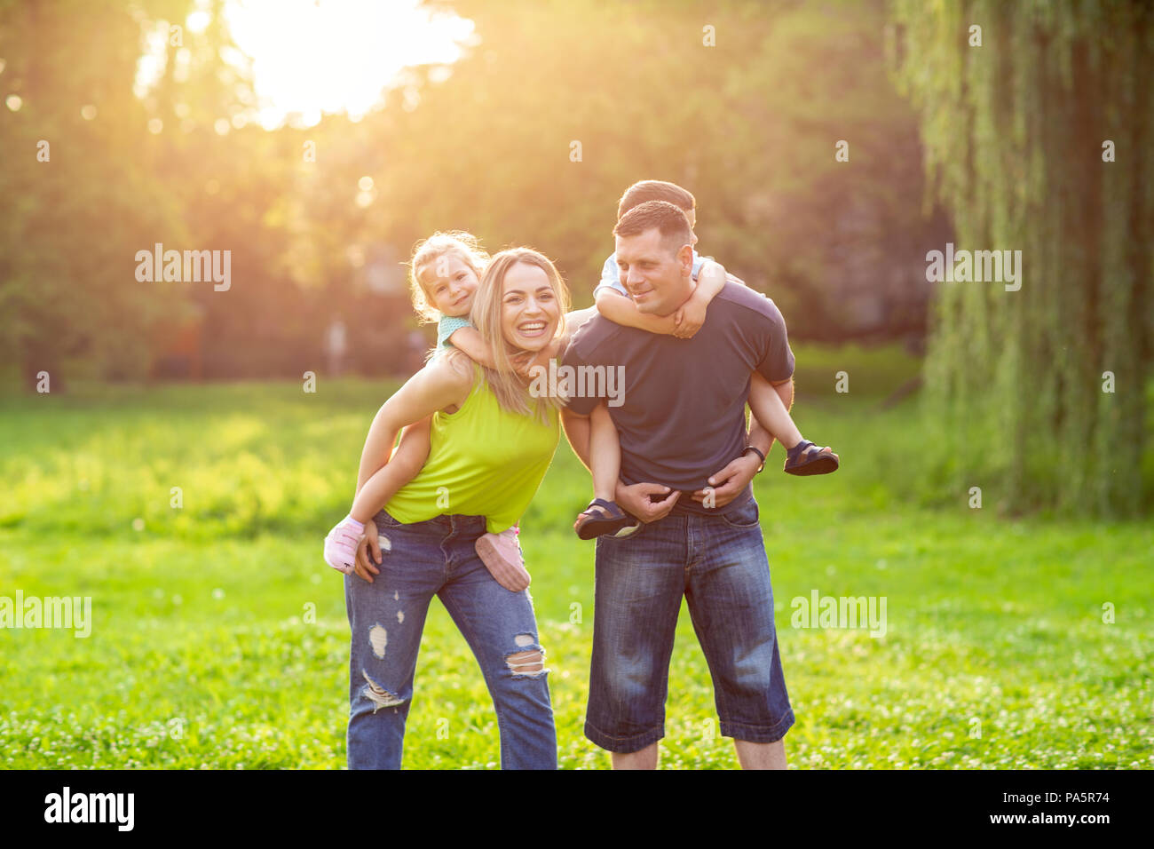 Family piggyback -Parents playing with their children in the park - Stock Image