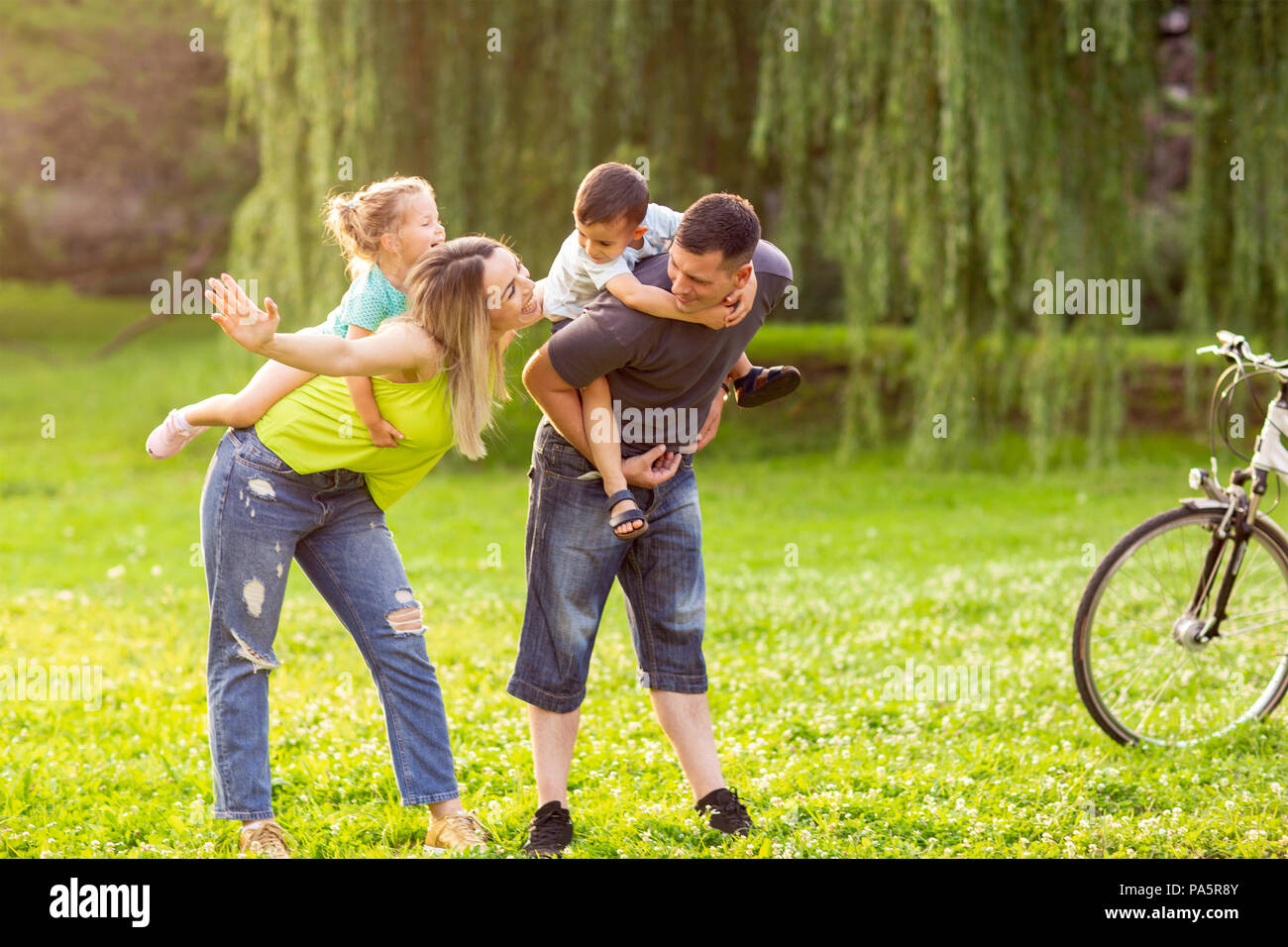 Family piggyback - Smiling young parents playing with their children in the park - Stock Image