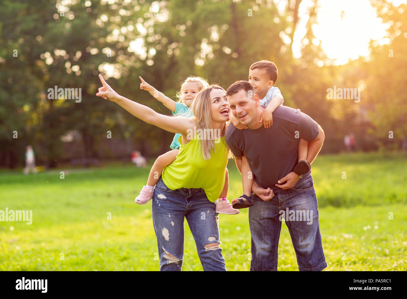 Funny young parents giving children piggyback ride in park - Stock Image
