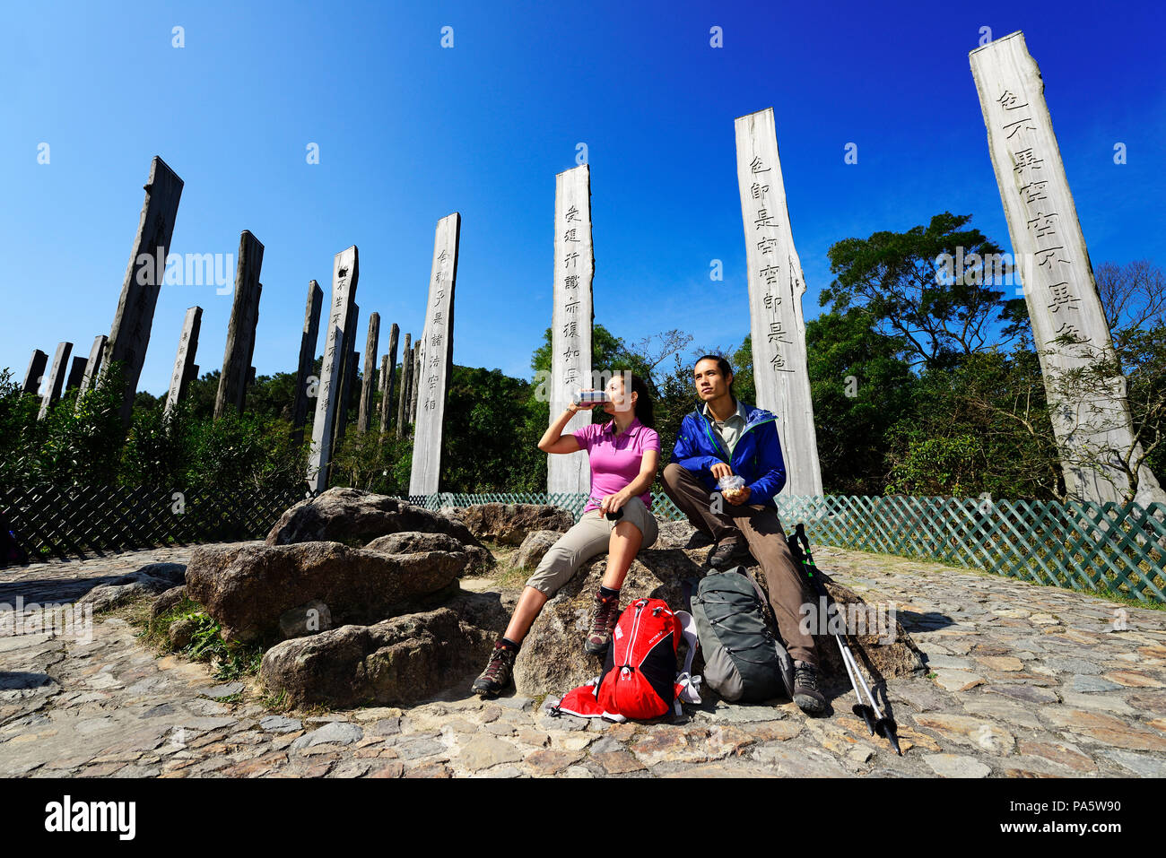 Hikers rest in front of wooden steles at Wisdom Path, Lantau Island, Hong Kong, China - Stock Image