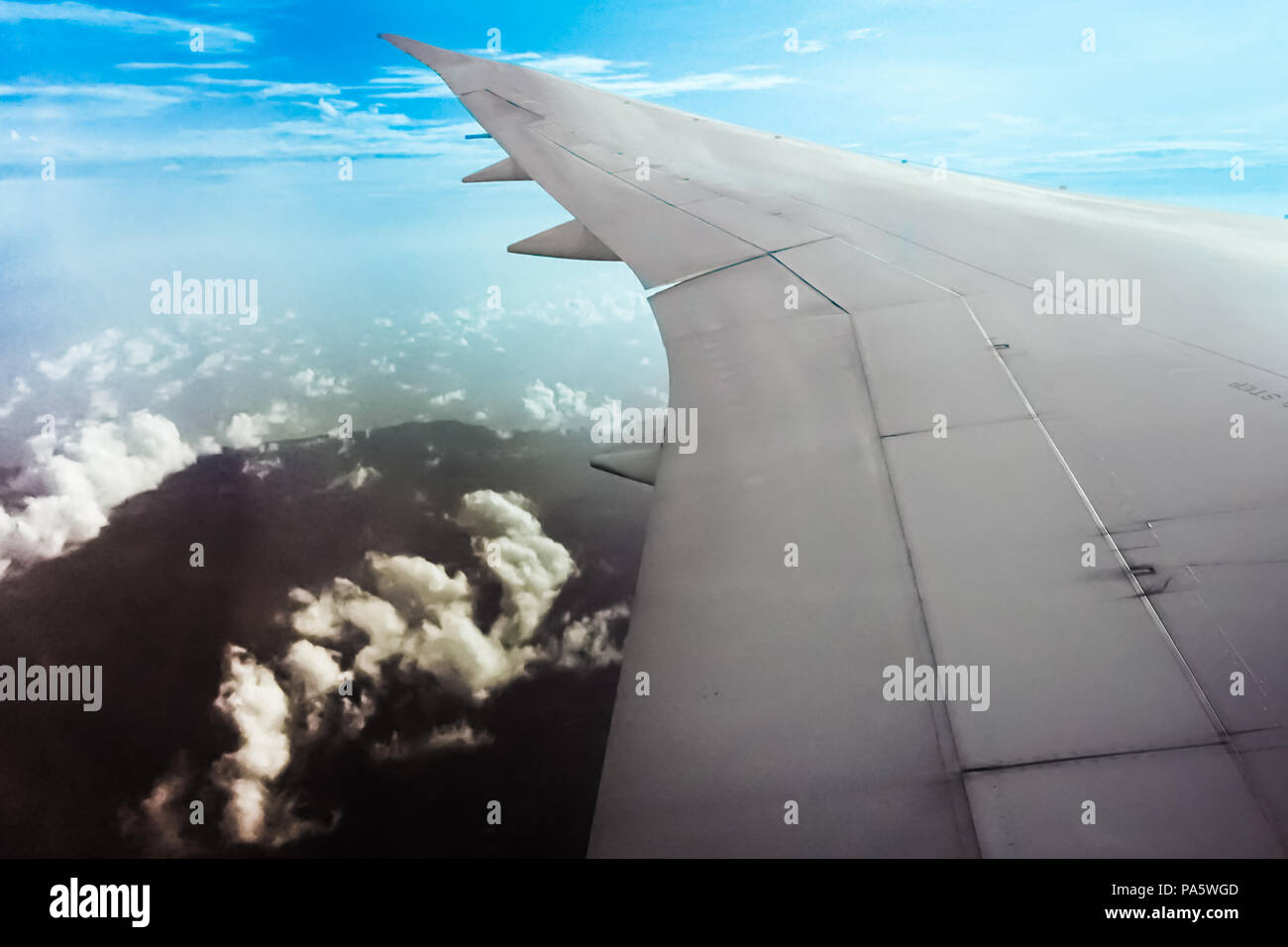 Commercial aircraft wing pointing in the blue sky evoke a wonderful feeling of space and depth. A fantastic view of the sky when looking through windo - Stock Image