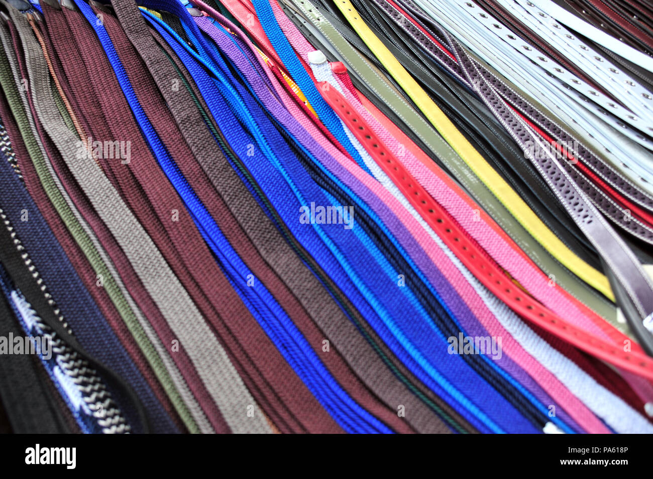 Colourful Mens belts on display at a clothes market held each week in Beziers, France - Stock Image