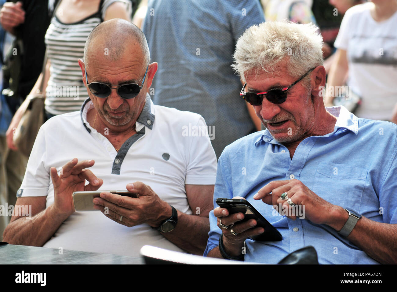 Two elderly men use their mobile phones whilst sitting at the cafe in the market held each week in Beziers, France - Stock Image