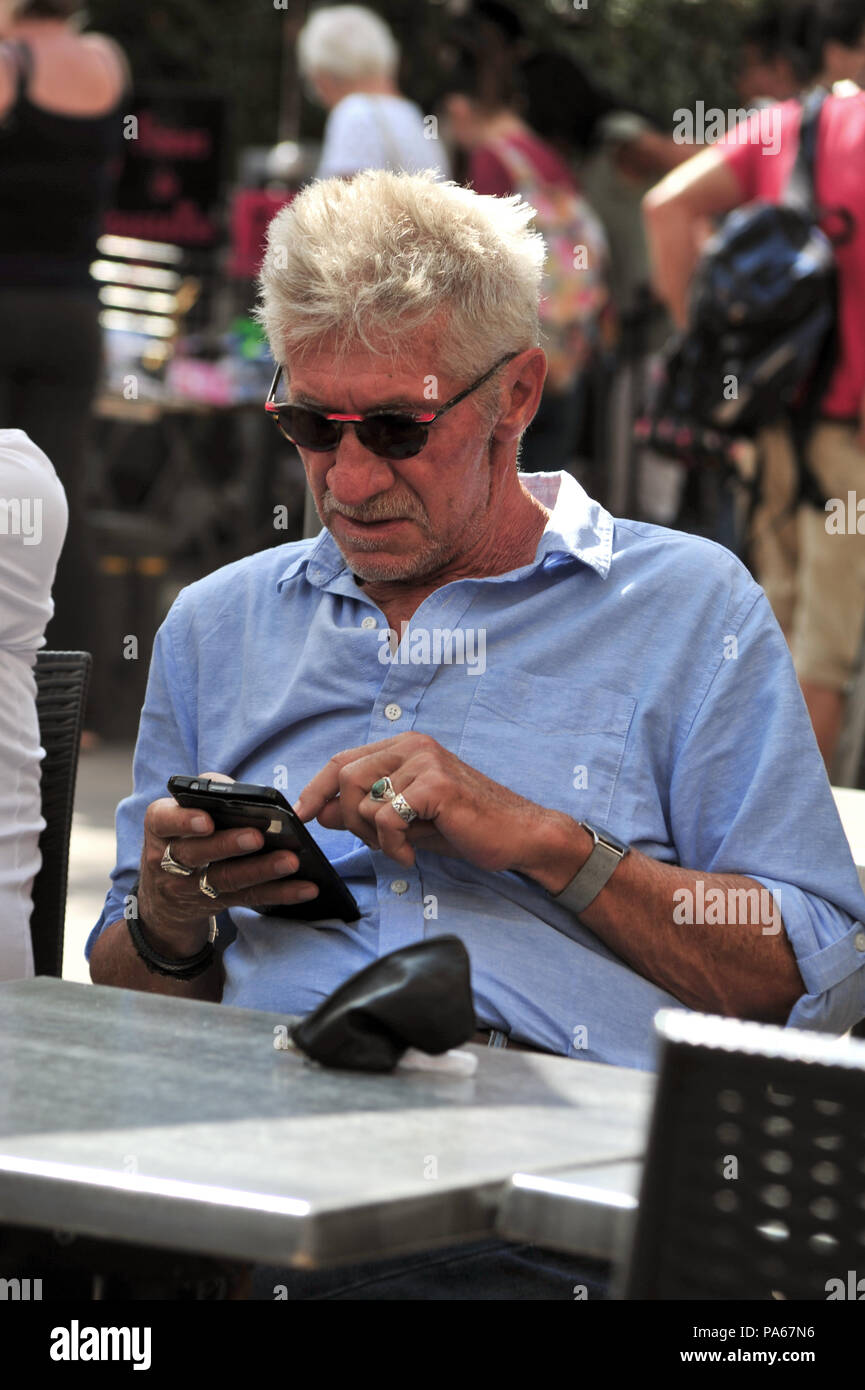 Two elderly men discussing the best way too use their mobile phones whilst sitting at the cafe in the market held each week in Beziers, France - Stock Image