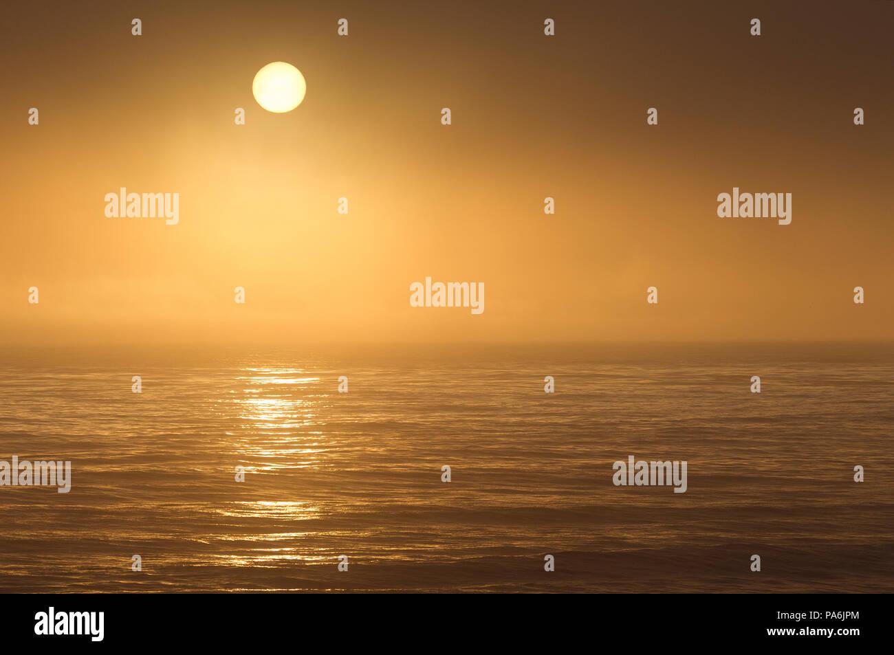 Sun Setting Through Fog over Pacific Ocean - Stock Image