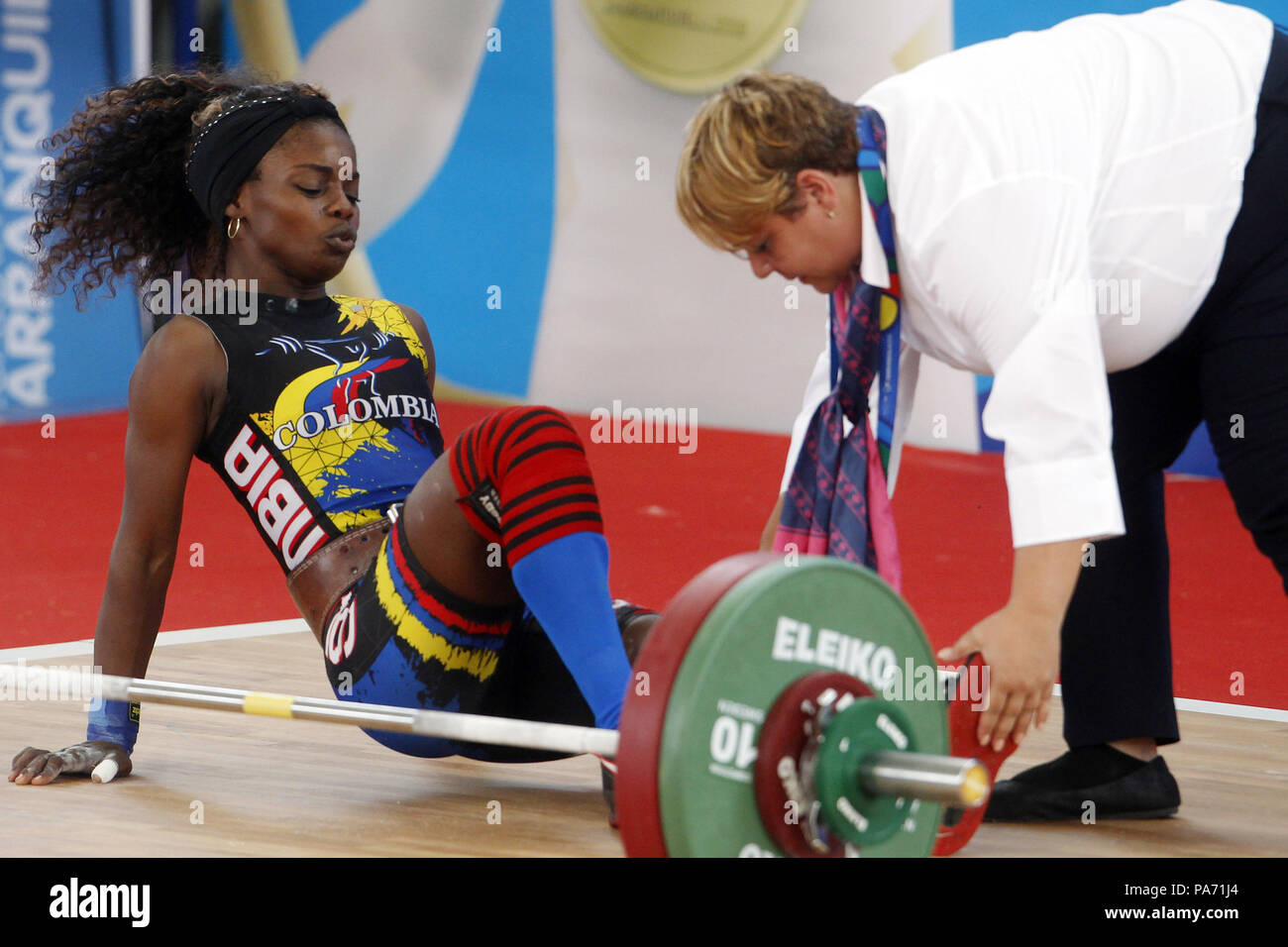 Barranquilla, Colombia. 20th July, 2018. Colombian Ana Iris Segura (L) receives medical attention after competing at 48kg women weighlifting during the Central American and Caribbean Games 2018, in Barranquilla, Colombia, 20 July 2018. Segura won the gold medal in 97kg. Credit: Luis Eduardo Noriega A./EFE/Alamy Live News - Stock Image