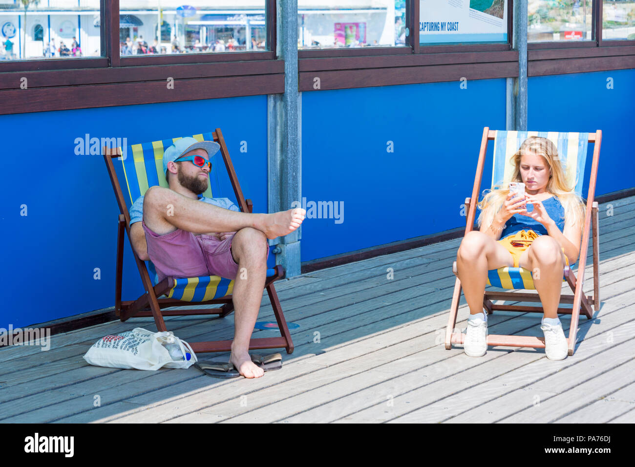 Bournemouth, Dorset, UK. 21st July 2018. UK weather: hot and sunny at Bournemouth beaches, as sunseekers head to the seaside to soak up the sun at the start of the summer holidays. In the shade or in the sun? Couple relaxing in deckchairs on Bournemouth Pier. Credit: Carolyn Jenkins/Alamy Live News - Stock Image