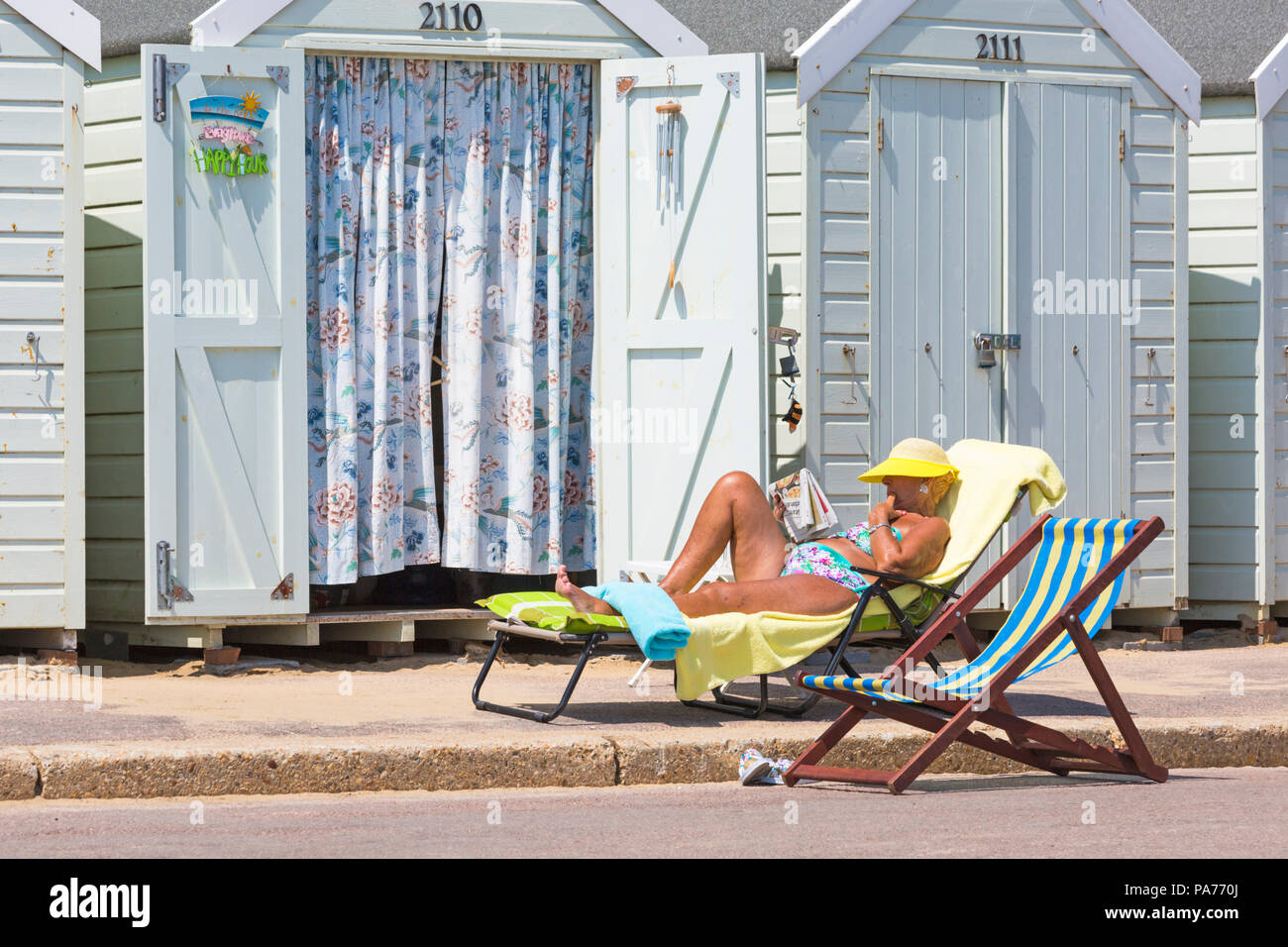 Bournemouth, Dorset, UK. 21st July 2018. UK weather: hot and sunny at Bournemouth beaches, as sunseekers head to the seaside to soak up the sun at the start of the summer holidays. Senior woman sunbathing reading newspaper on sunlounger outside beach huts. Credit: Carolyn Jenkins/Alamy Live News - Stock Image