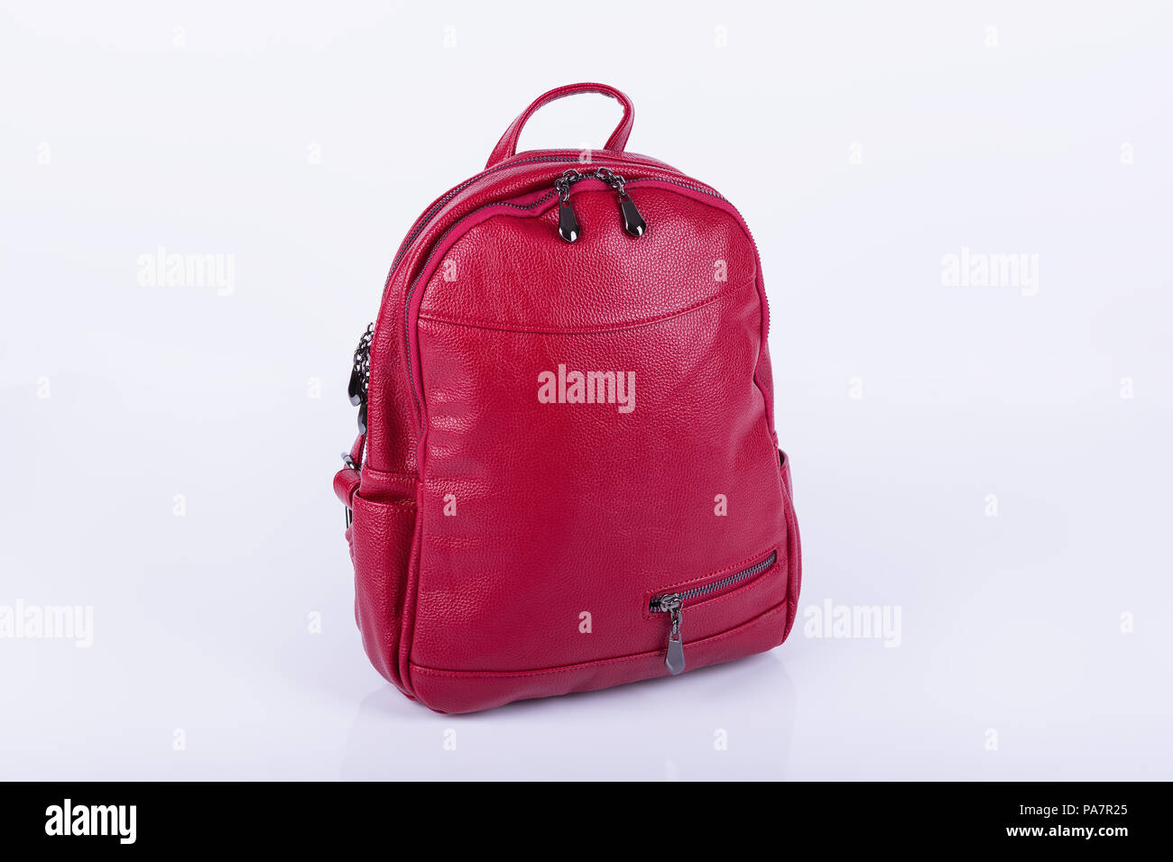 Red leather fashionable female backpack on white background. - Stock Image a71ebd94d7023