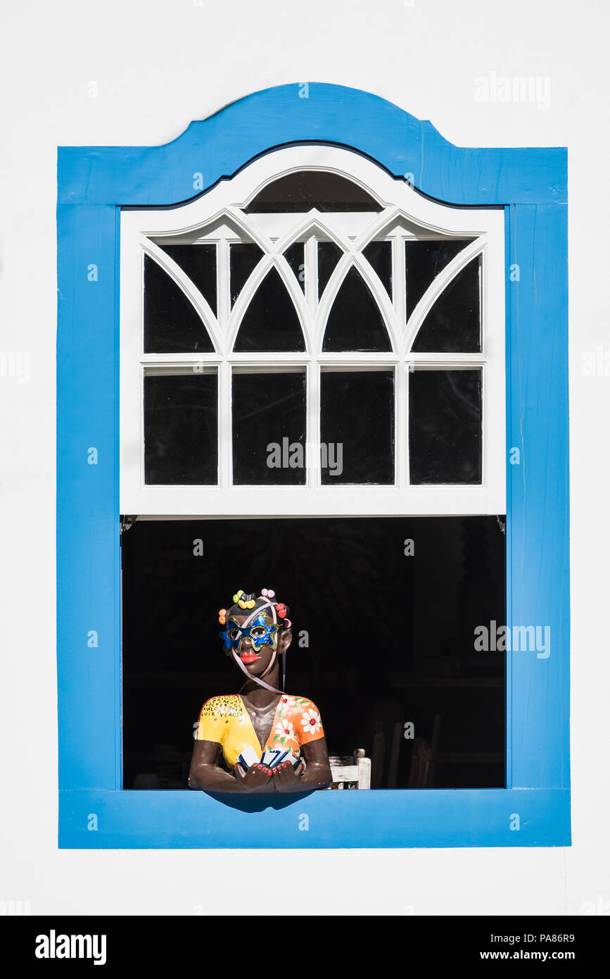 Paraty, Brazil - February 28, 2017: Traditional brazilian souvenir girl at the country house window in historic town Paraty, Rio de Janeiro state, Bra - Stock Image