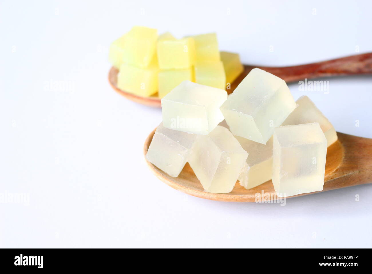 Close up of sliced transparent and yellow cocoon glycerin soap bases on white background. - Stock Image