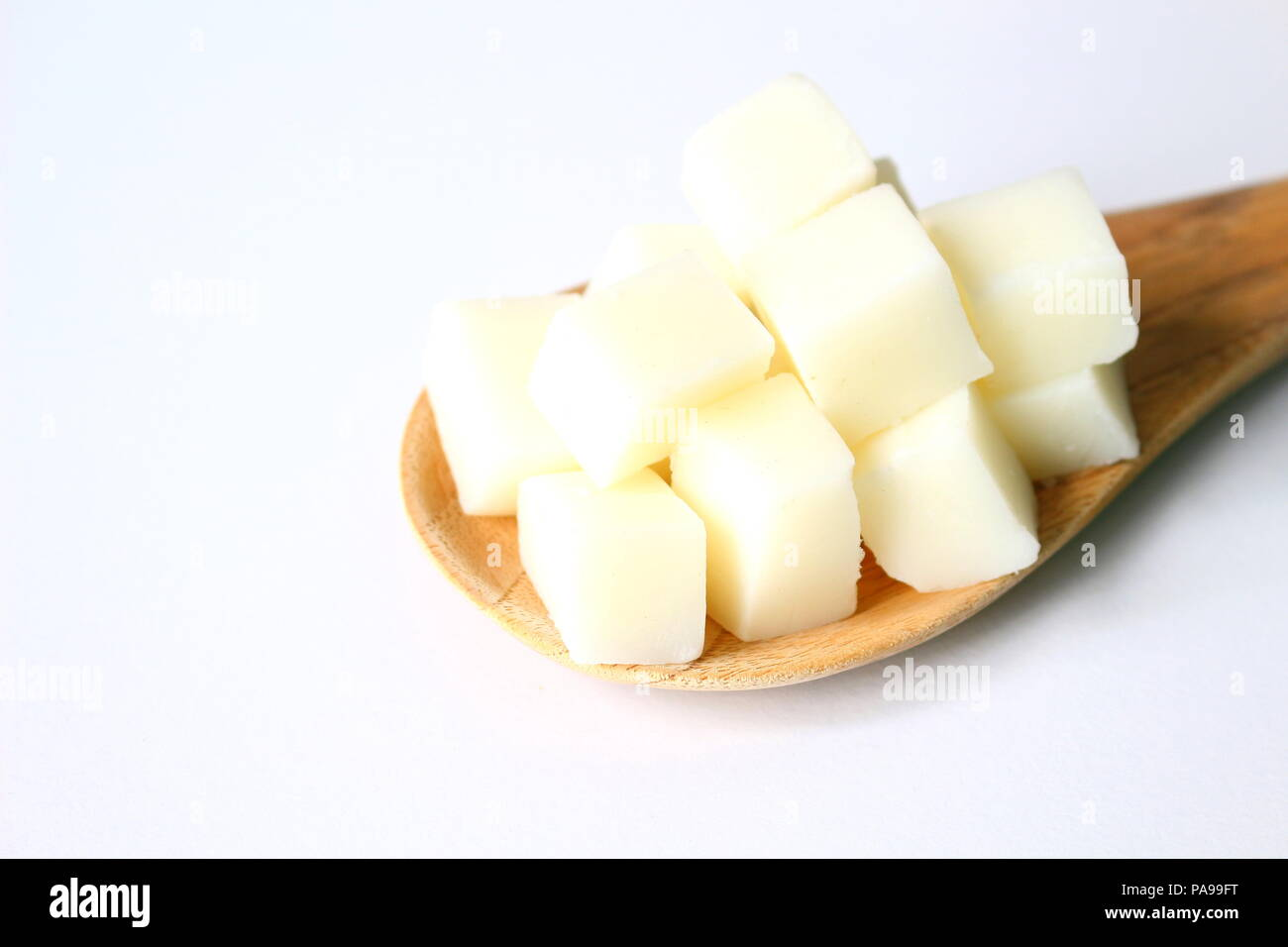 Close up of sliced white glycerin soap bases on wooden paddle on white background. - Stock Image