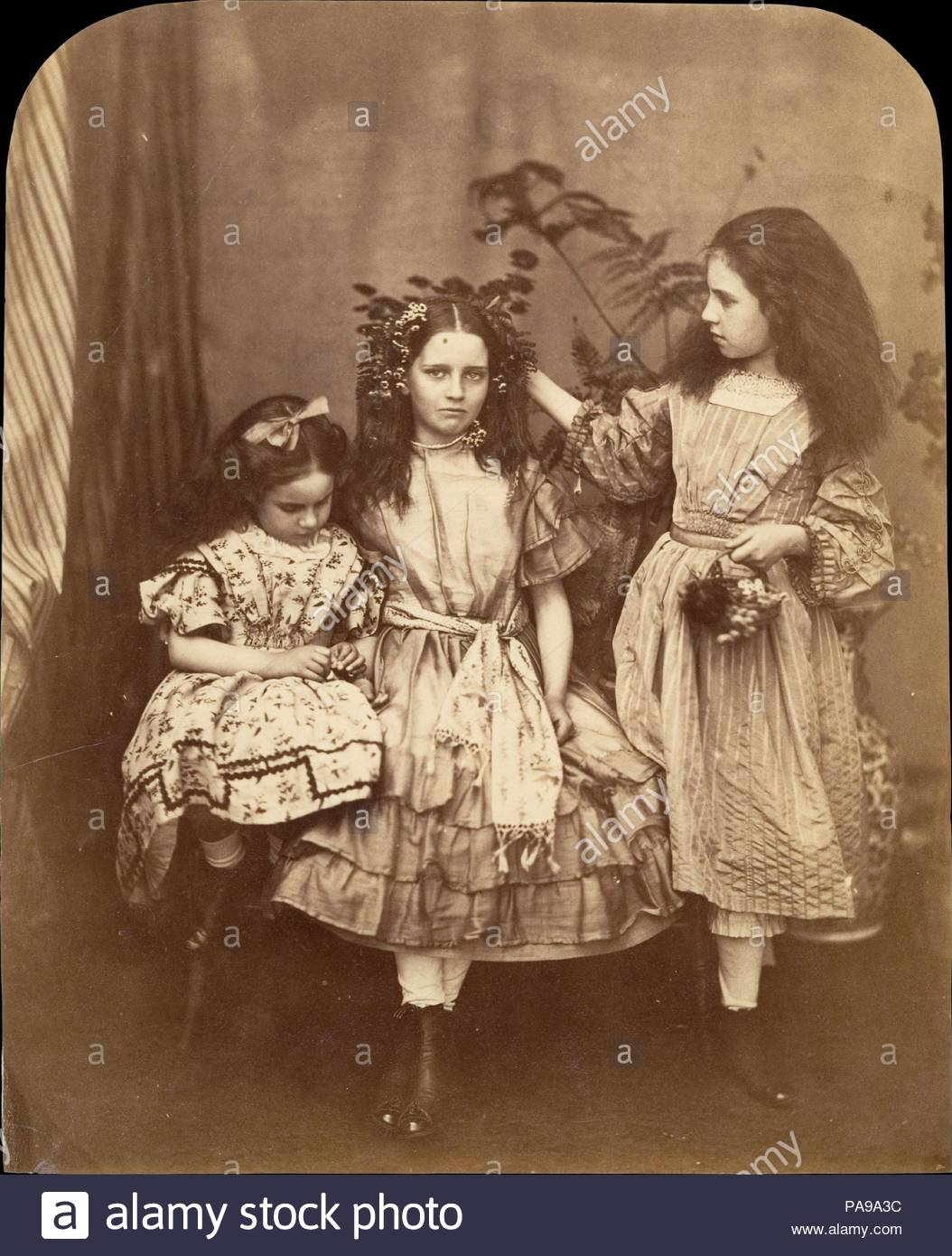 Flora Rankin, Irene MacDonald, and Mary Josephine MacDonald at Elm Lodge. Artist: Lewis Carroll (British, Daresbury, Cheshire 1832-1898 Guildford). Dimensions: 22.2 x 18 cm (8 3/4 x 7 1/16 in.). Subject: Flora Rankin (British); Irene MacDonald (British, born 1857); Mary Josephine MacDonald (British, 1853-1878). Date: July 1863.  Irene and Mary MacDonald were two of the five children of Scottish novelist and poet George MacDonald. Carroll was a friend of the family, and the children affectionately called him 'Uncle.' It was the MacDonalds to whom he read the manuscript of The Adventures of Alic - Stock Image