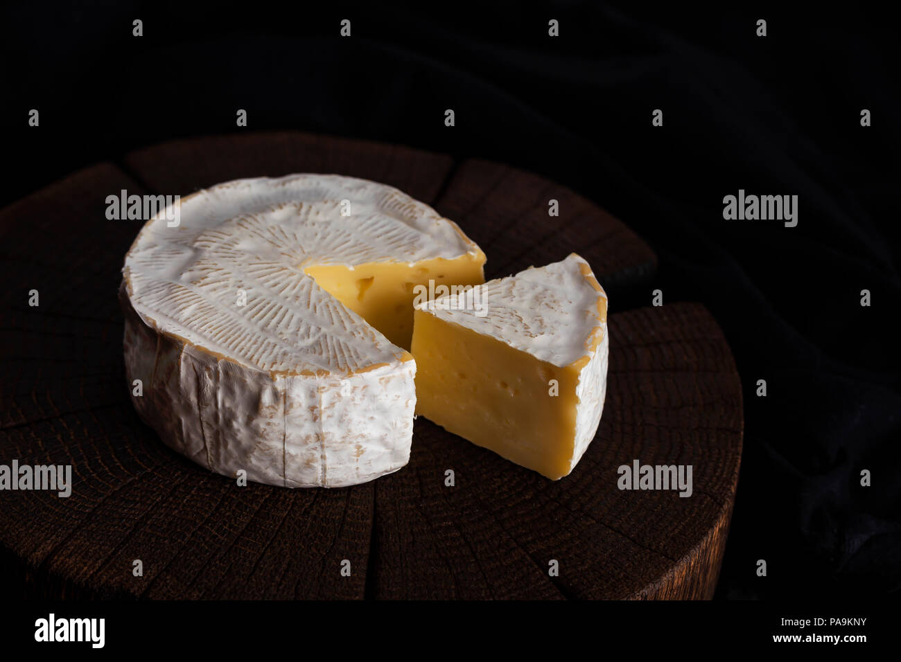 Camembert cheese on black wooden background, with copy space. Shallow depth of field - Stock Image