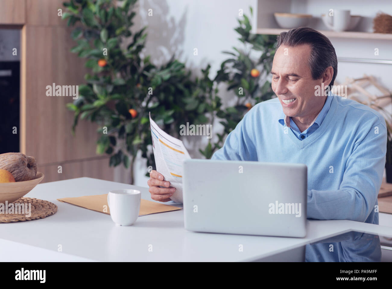 Nice aged man reading a newspaper - Stock Image