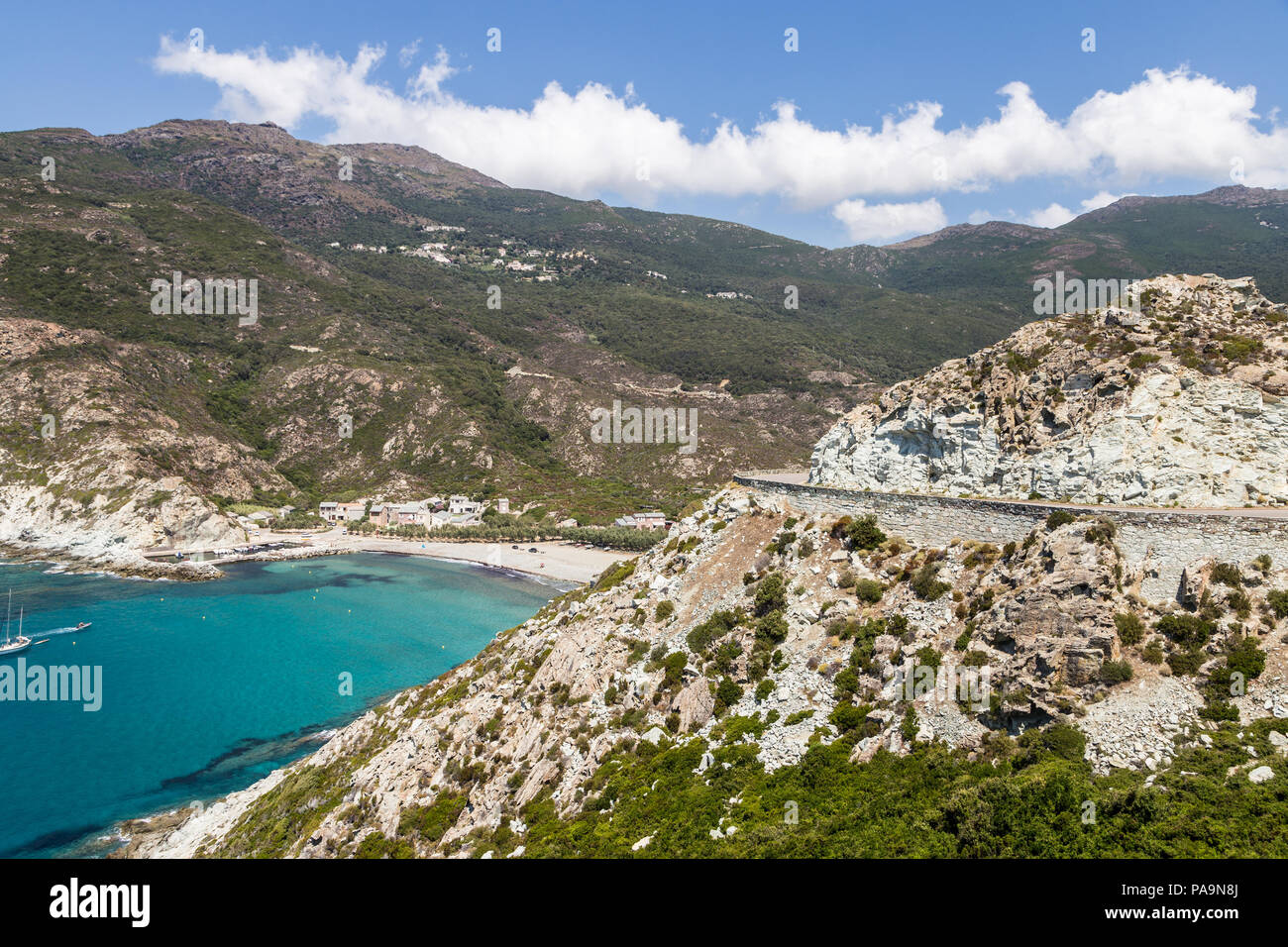 Stunning coastal road by a beautiful bay with turquoise water in Corsica in France near the Ile Rousse village. - Stock Image