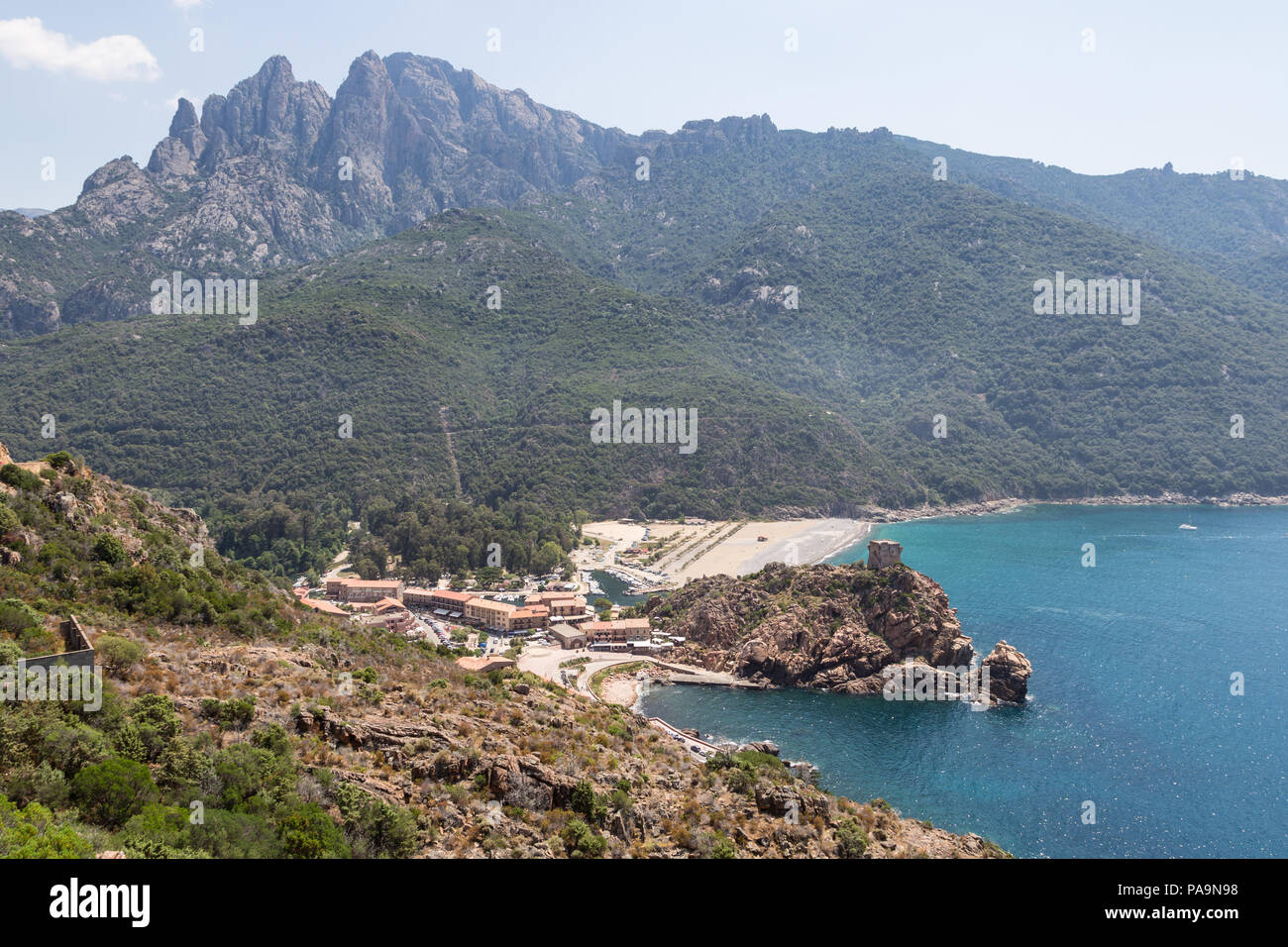 The resort town of Porto with its medieval fortification tower on a cliff by the mediterranean sea in Corsica, France - Stock Image