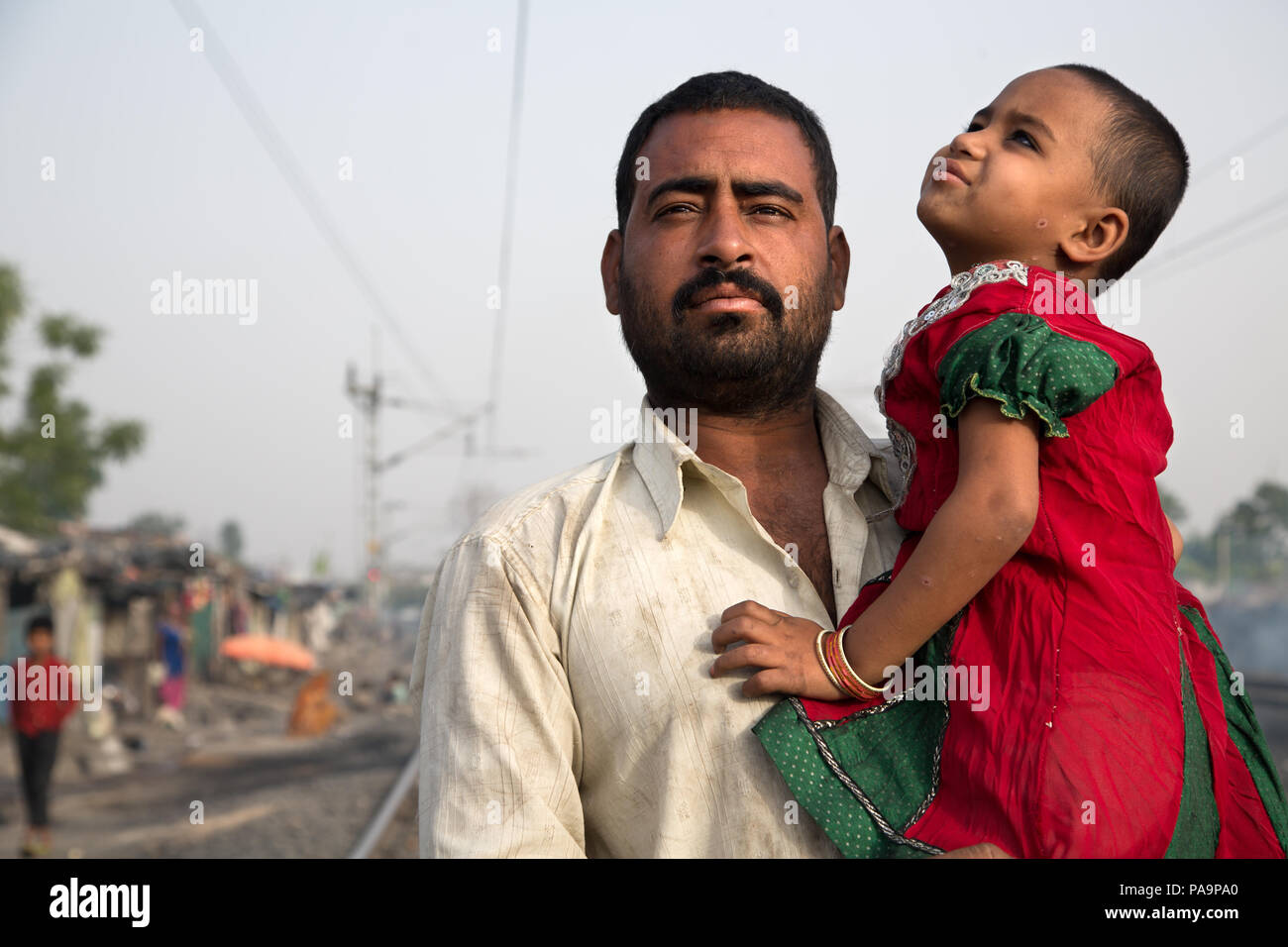 Father and his disabled daughter in Arif Nagar area, near the abandoned Union Carbide industrial complex, Bhopal, India - Stock Image