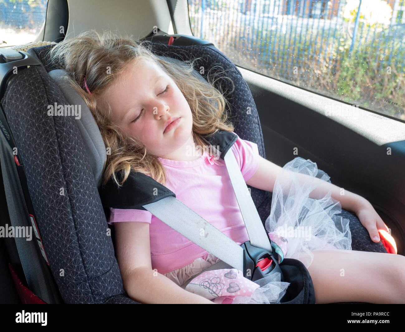 Three year old child sleeping in her car seat, UK - Stock Image
