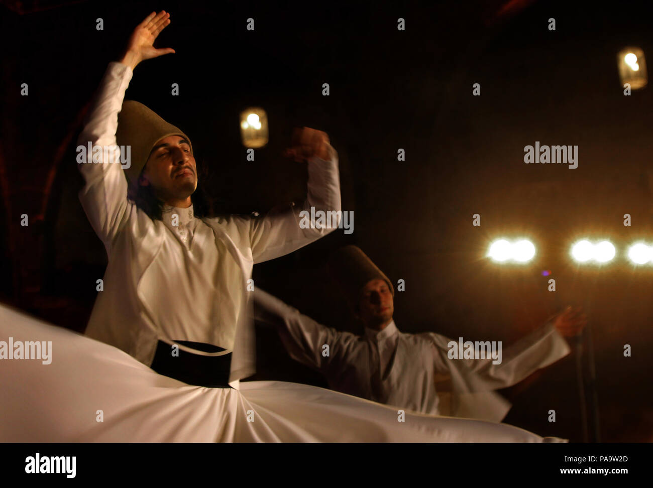 Whirling  dervishes from Turkey perform during the holy month of Ramadan at the historical Khan al-Franj in the southern Lebanese port city of Sidon. - Stock Image