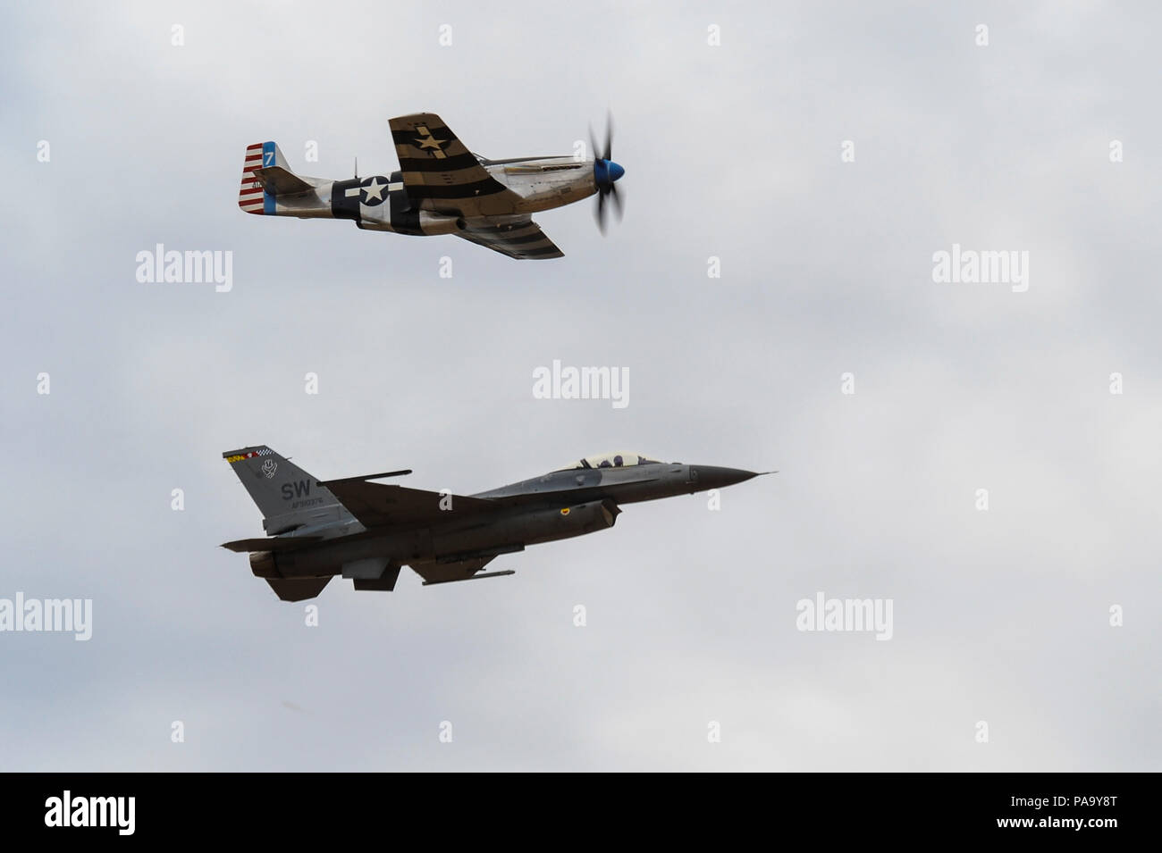 A P-51 Mustang and an F-16C Fighting Falcon fly in formation together during the 2016 Heritage Flight Training and Certification Course at Davis-Monthan Air Force Base, Ariz., March 6, 2016. Established in 1997, the HFTCC certifies civilian pilots of historic military aircraft and U.S. Air Force pilots to fly in formation together during the upcoming air show season. (U.S. Air Force photo by Airman 1st Class Mya M. Crosby/Released) - Stock Image