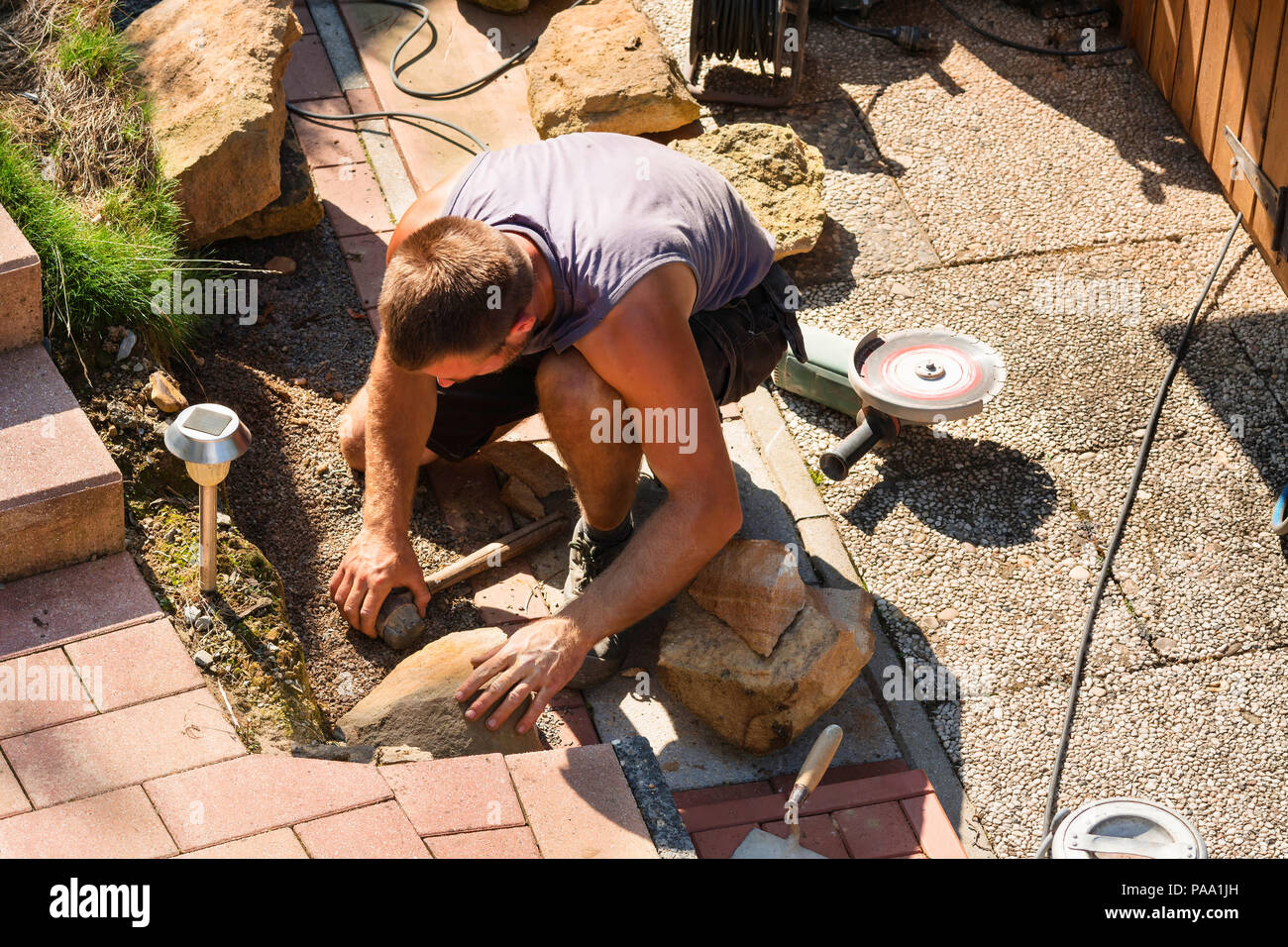 Man Build a dry wall in the garden. In the background, various tools. - Stock Image