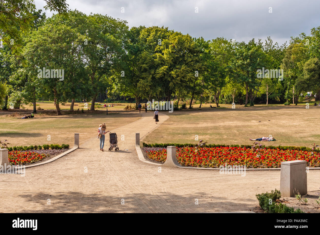 People are walking in a Dublin park on a hot summer day. - Stock Image