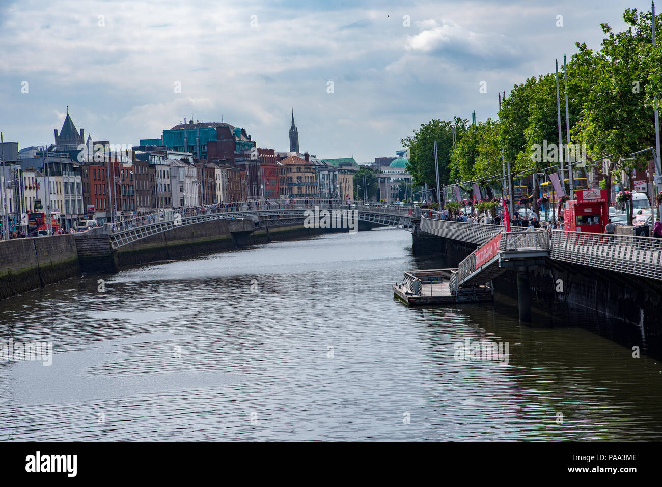 Pedestrians, flats and tour tour busses on the banks of the River Liffey. - Stock Image