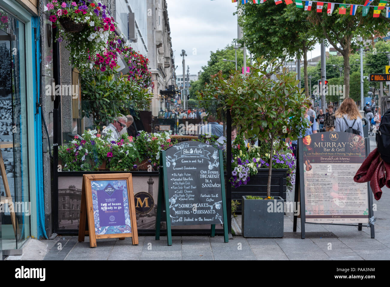 Patrons are seated at an outdoor Bar & Grill in Dublin, surrounded by flowers as pedestrians pass by. - Stock Image