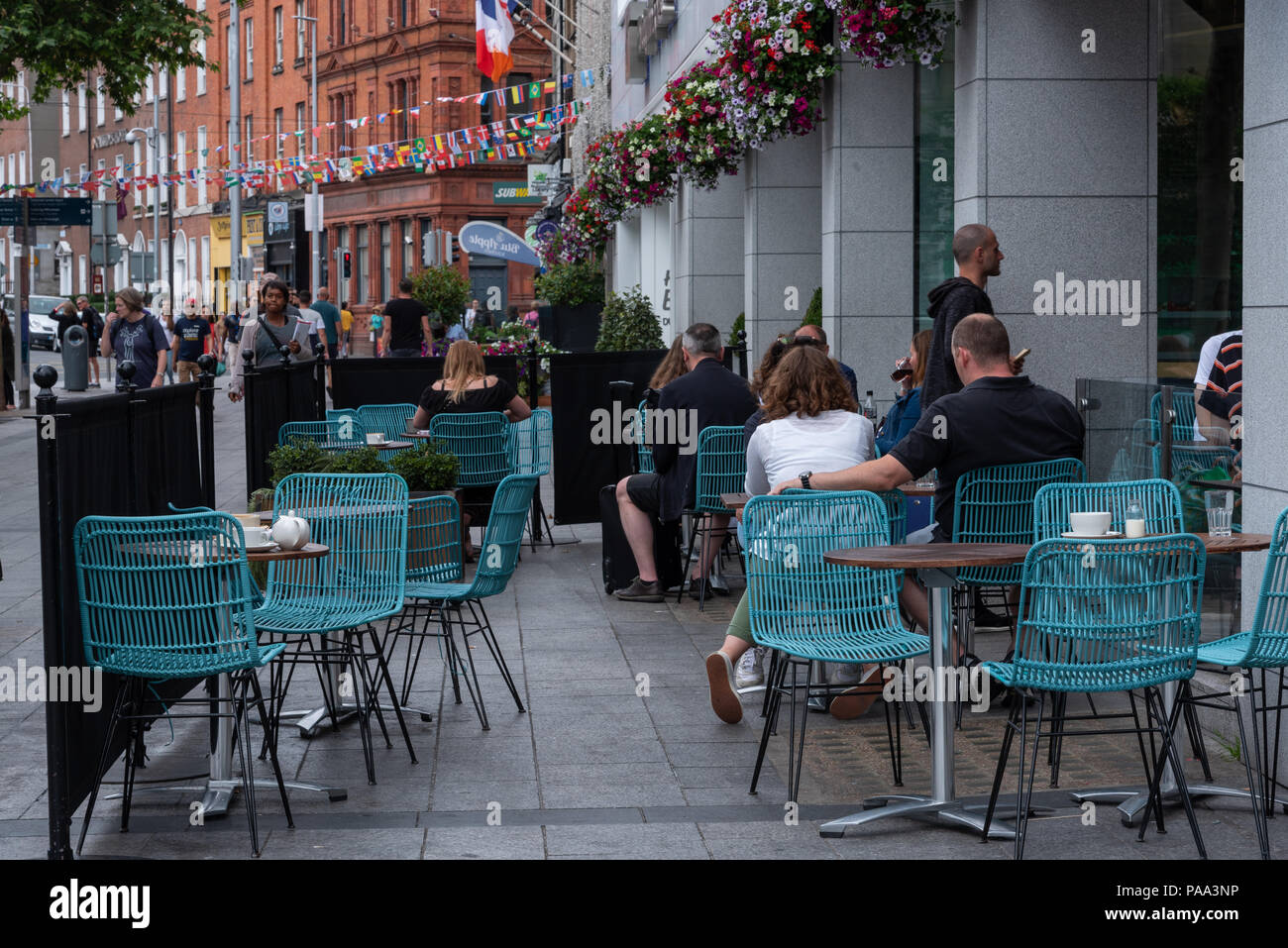 People sitting at an outdoor cafe in Dublin, Ireland having coffee while nearby pedestrians walk past. - Stock Image
