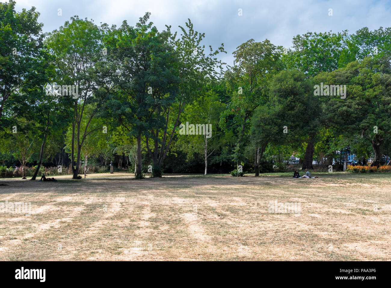 People relaxing in the shade at a Dublin City park on a hot summer day; the parched ground below reflects the dry summer. - Stock Image