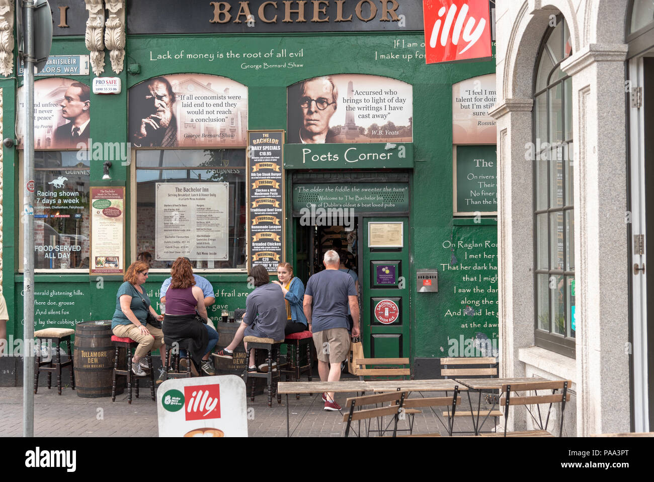 People sit down and enjoy a pint outside a pub in Ireland. A man is entering the doorway. - Stock Image